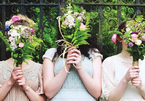 Three Bridesmaids Holding Bouquets Outdoors