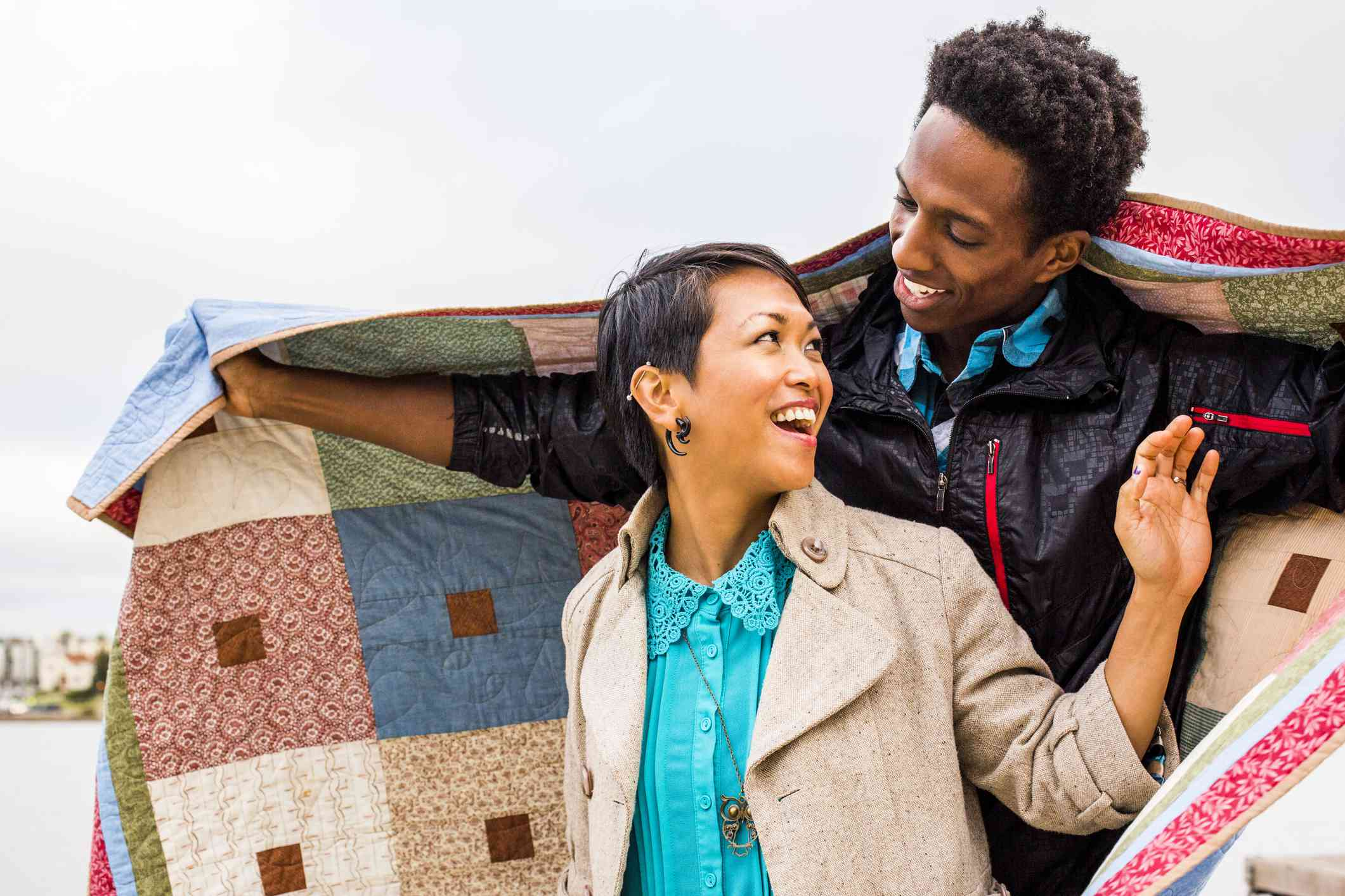 Couple wrapping themselves in a quilt