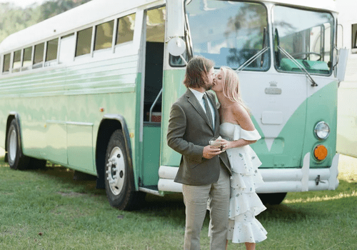 Couple kissing in front of a green, retro bus