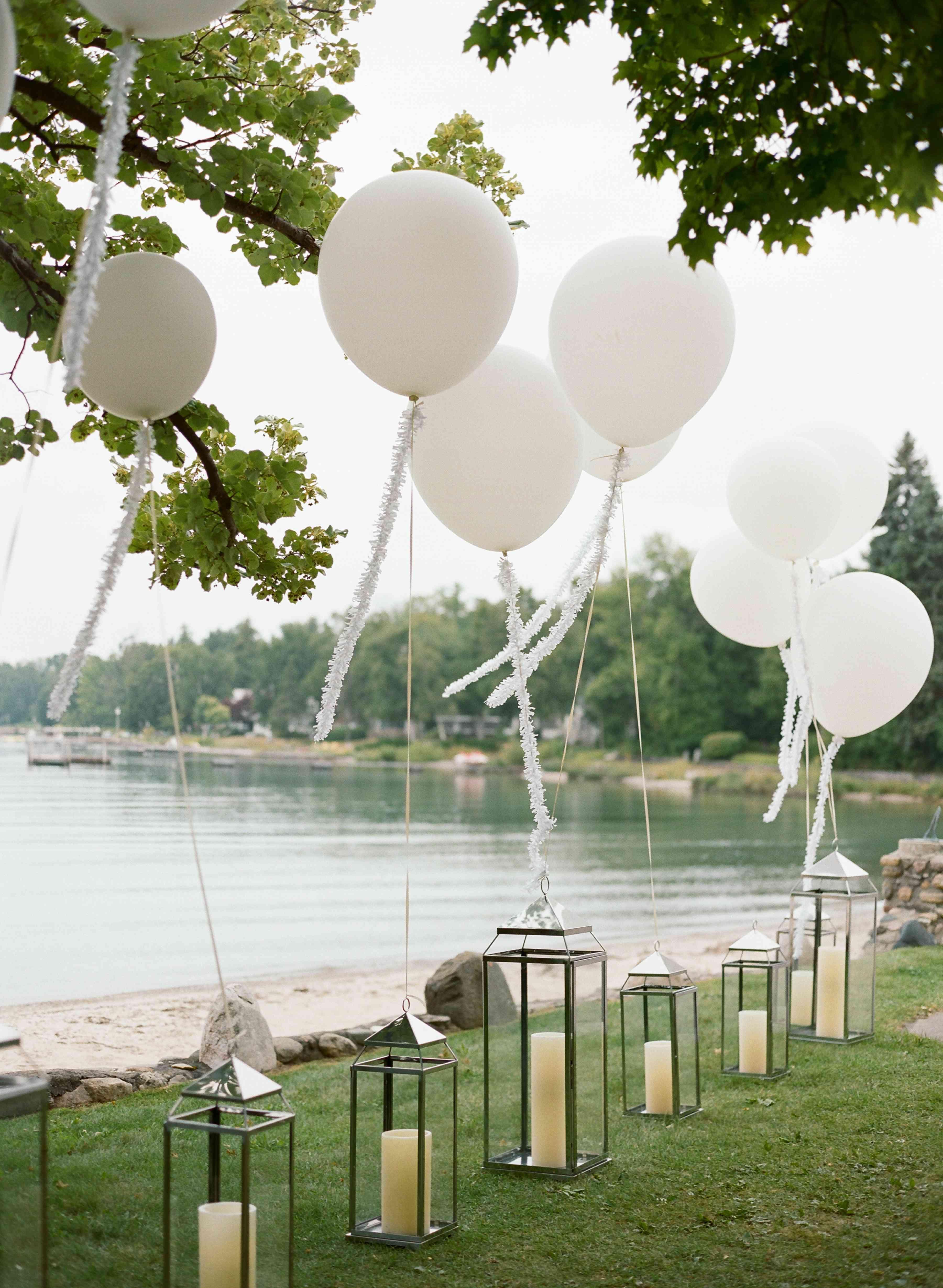 White balloons tied to lanterns beside a lake