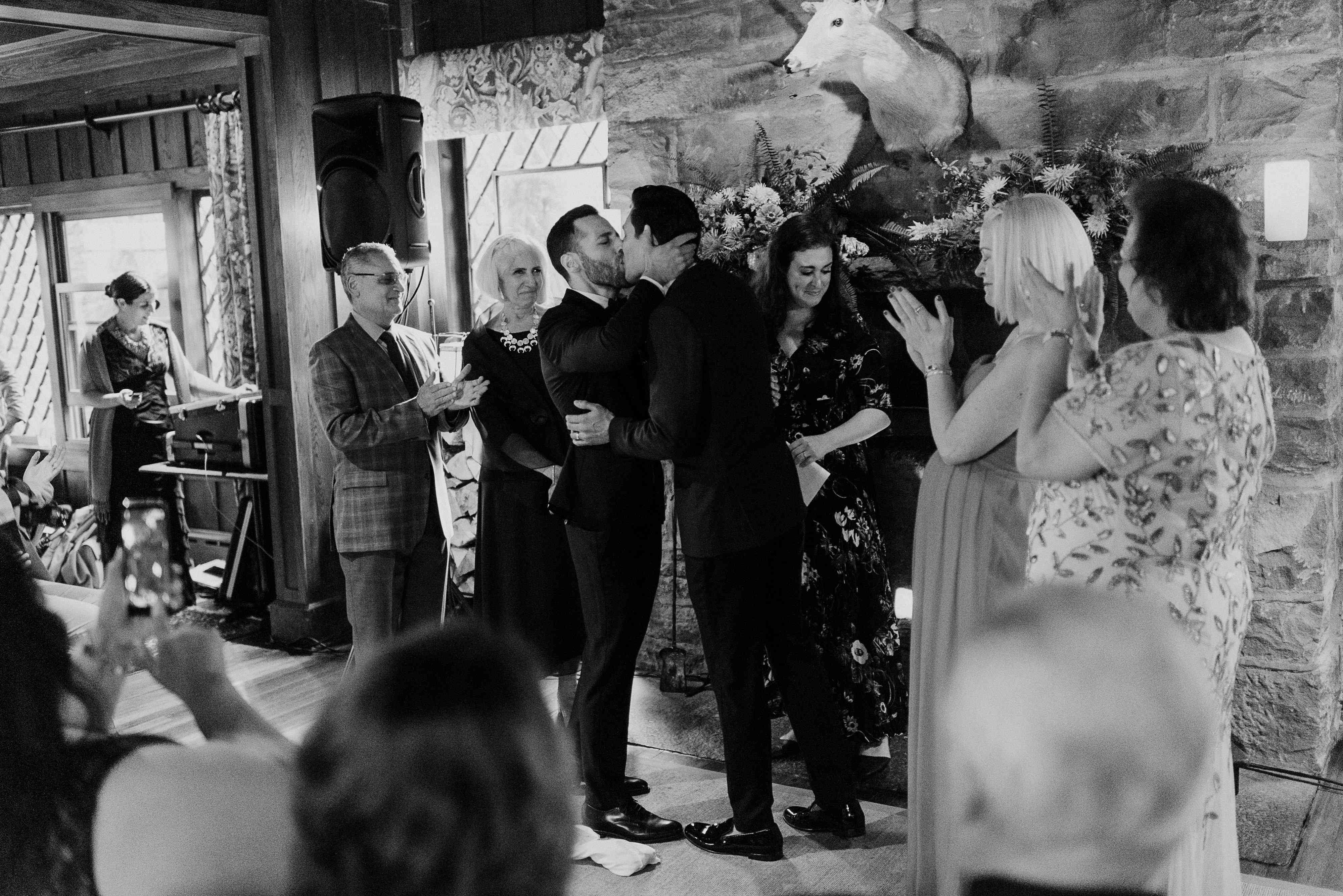 Grooms kissing at ceremony
