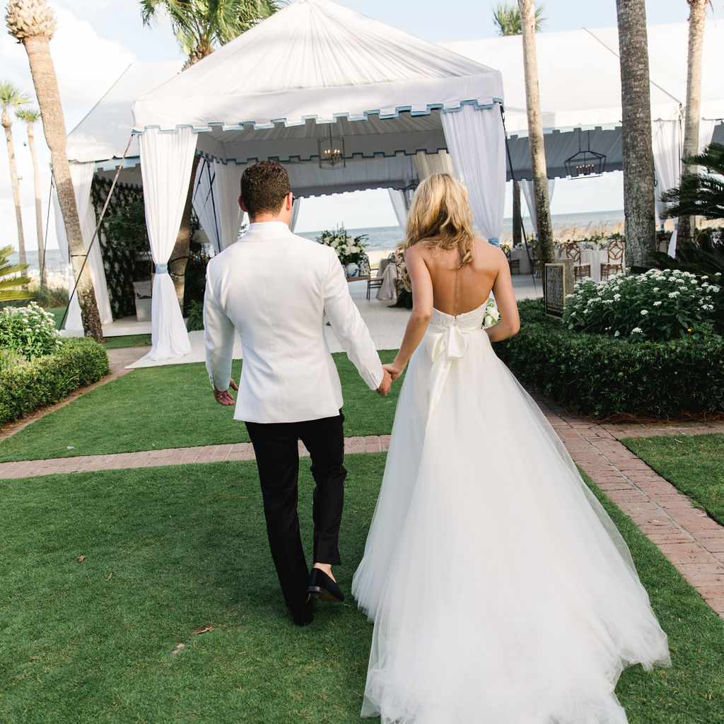 timeless southern wedding, bride and groom holding hands reception