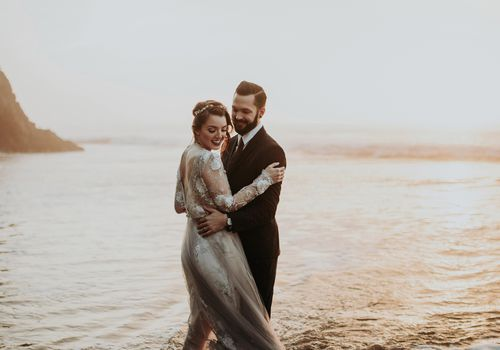Couple smiling in the ocean during golden hour