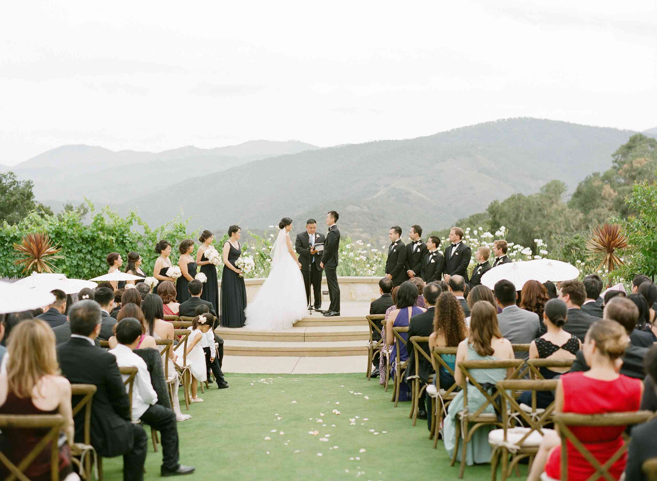 Wedding ceremony surrounded by greenery with mountains in the background