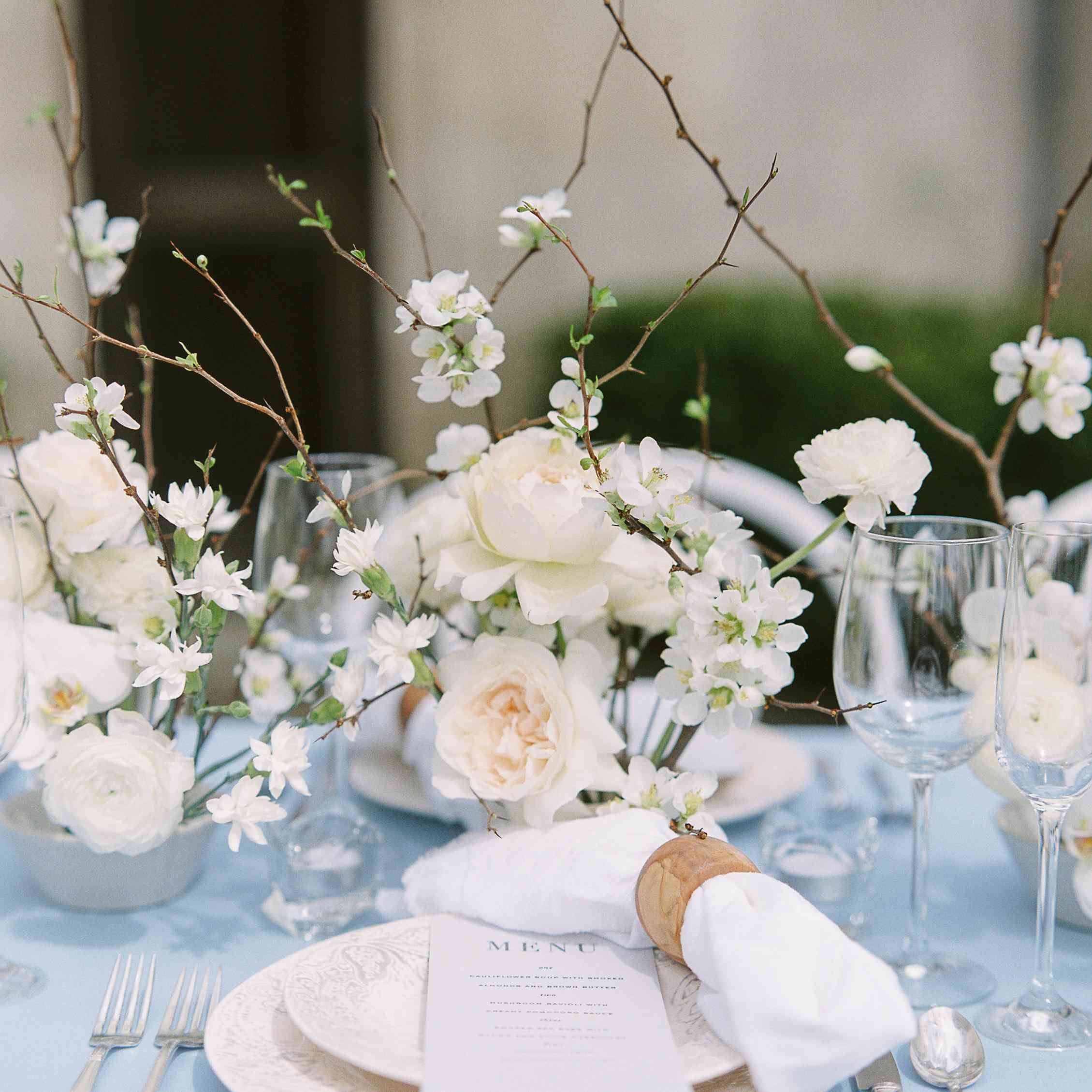 Table setting incorporating branches and white flowers
