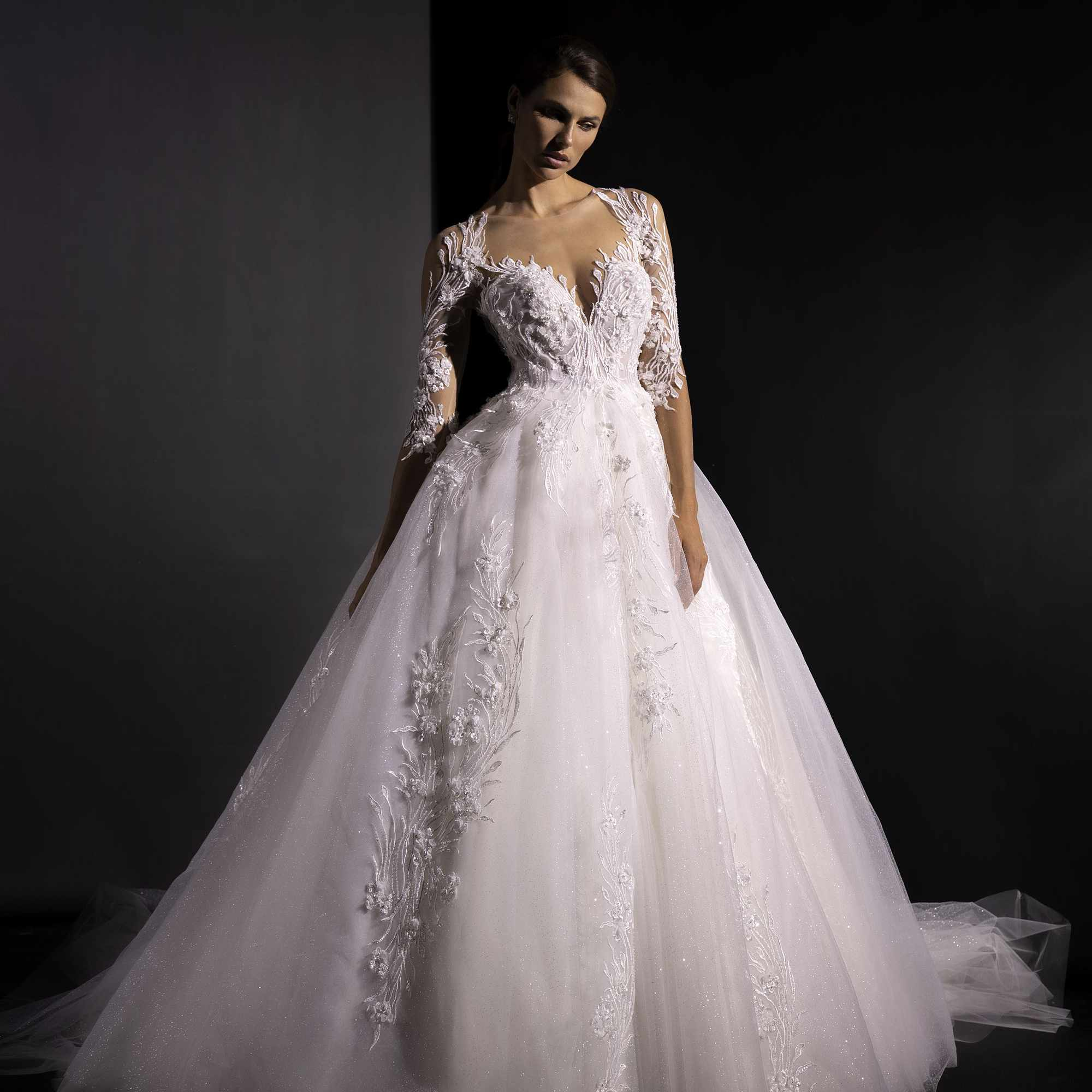 Model in three-quarter-sleeve ballgown with a tulle skirt, deep sweetheart bodice, and 3D floral embroidery