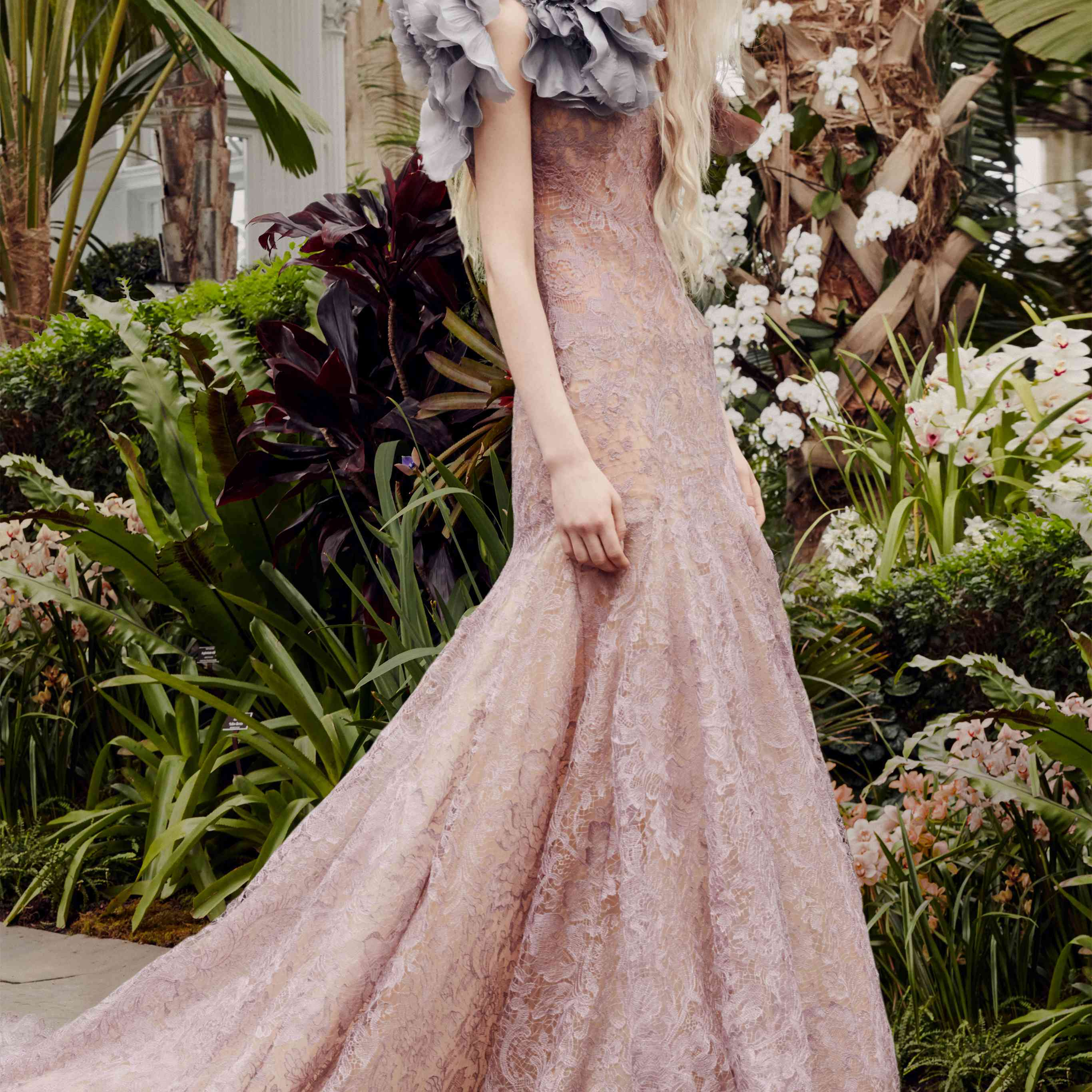 Model in a pink lace mermaid gown with a gray flower accent at the shoulder