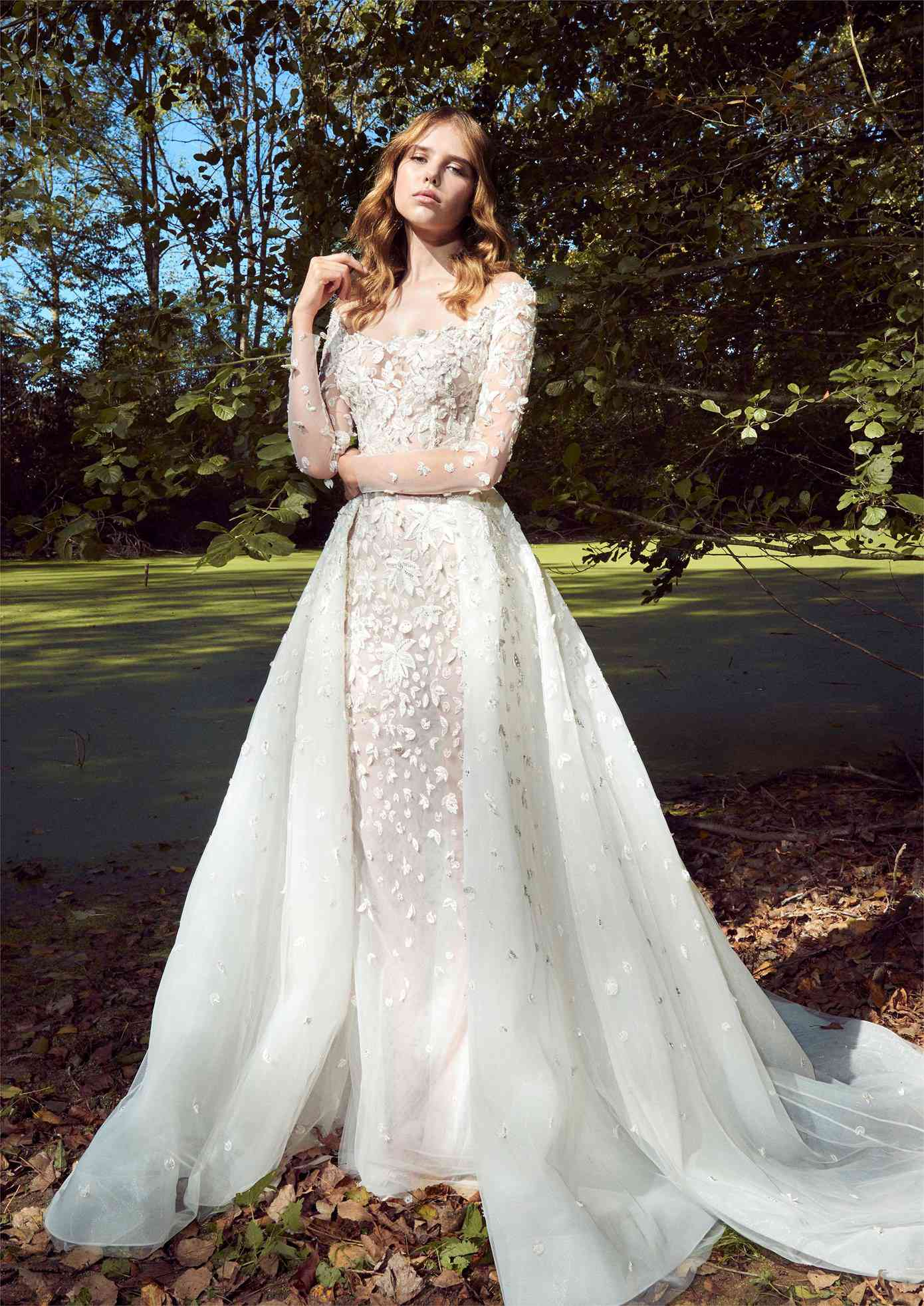 Model in off-the-shoulder long-sleeve gown with allover floral appliques and a matching overskirt