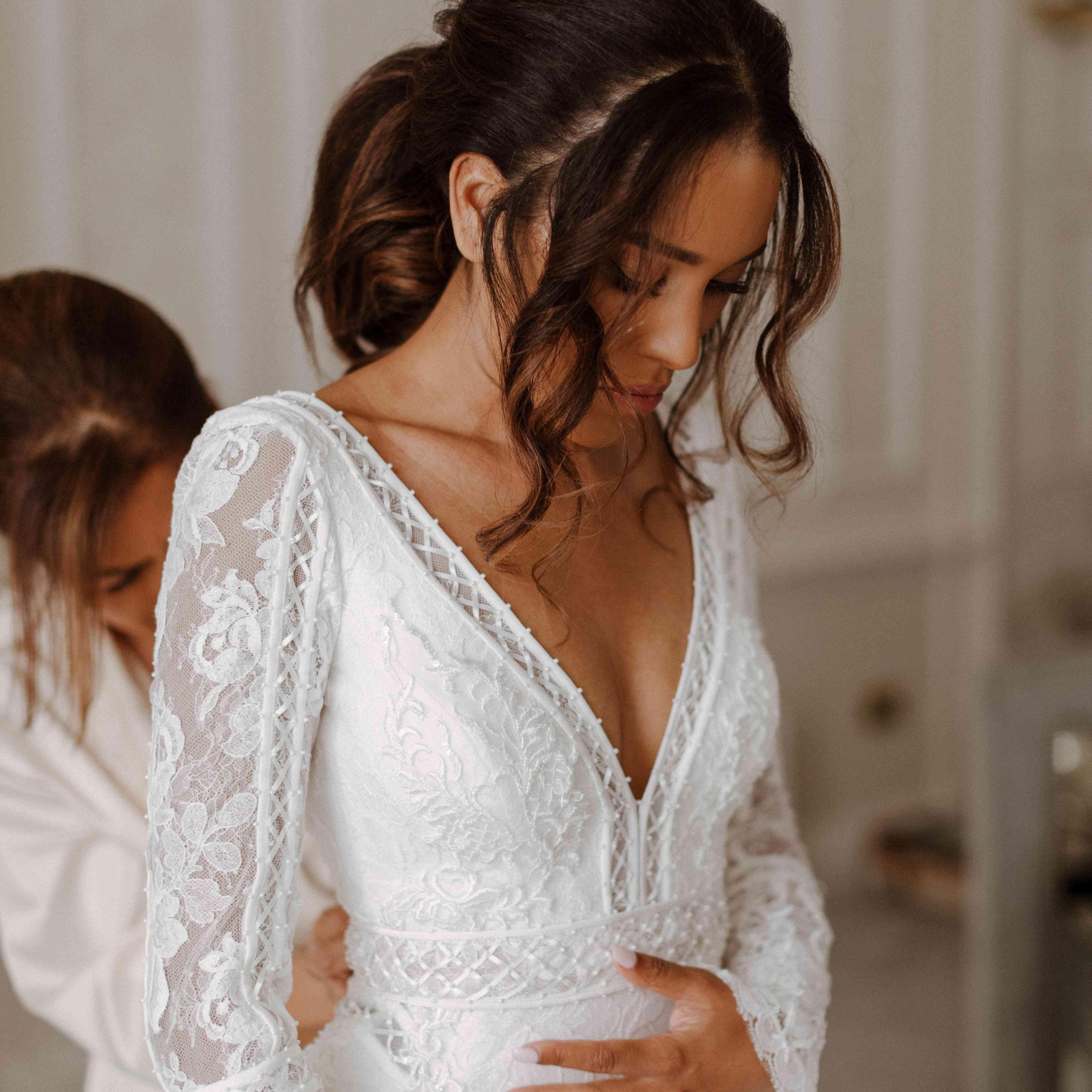 bride getting ready in long sleeve dress