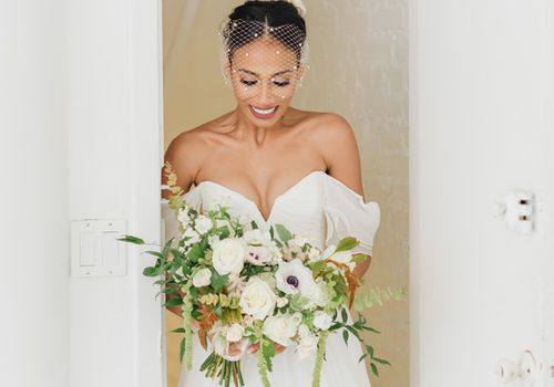 Bride with birdcage veil smiling and looking down at white and green bouquet