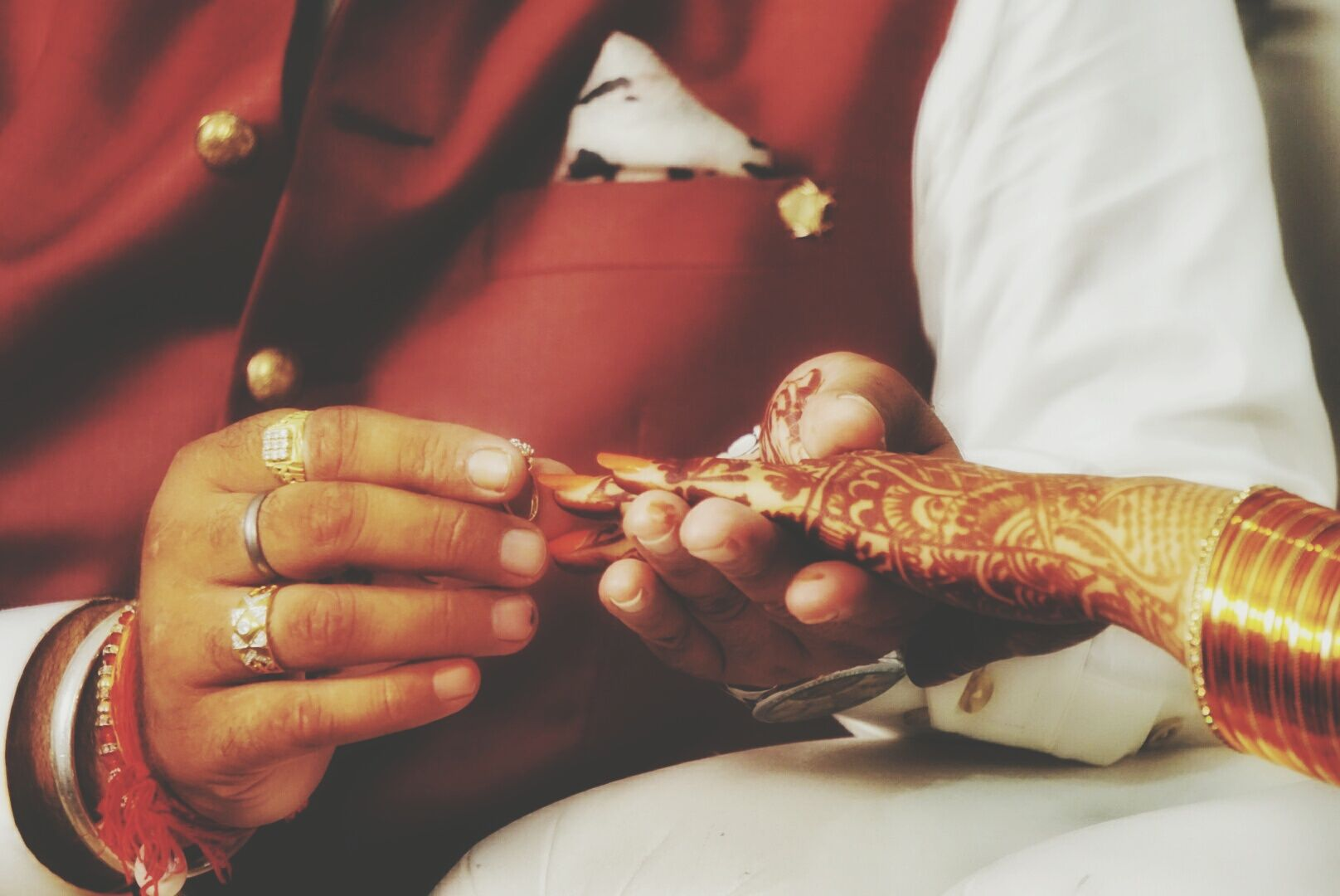 Groom-to-be putting an engagement ring on bride-to-be's finger at a Hindu engagement ceremony