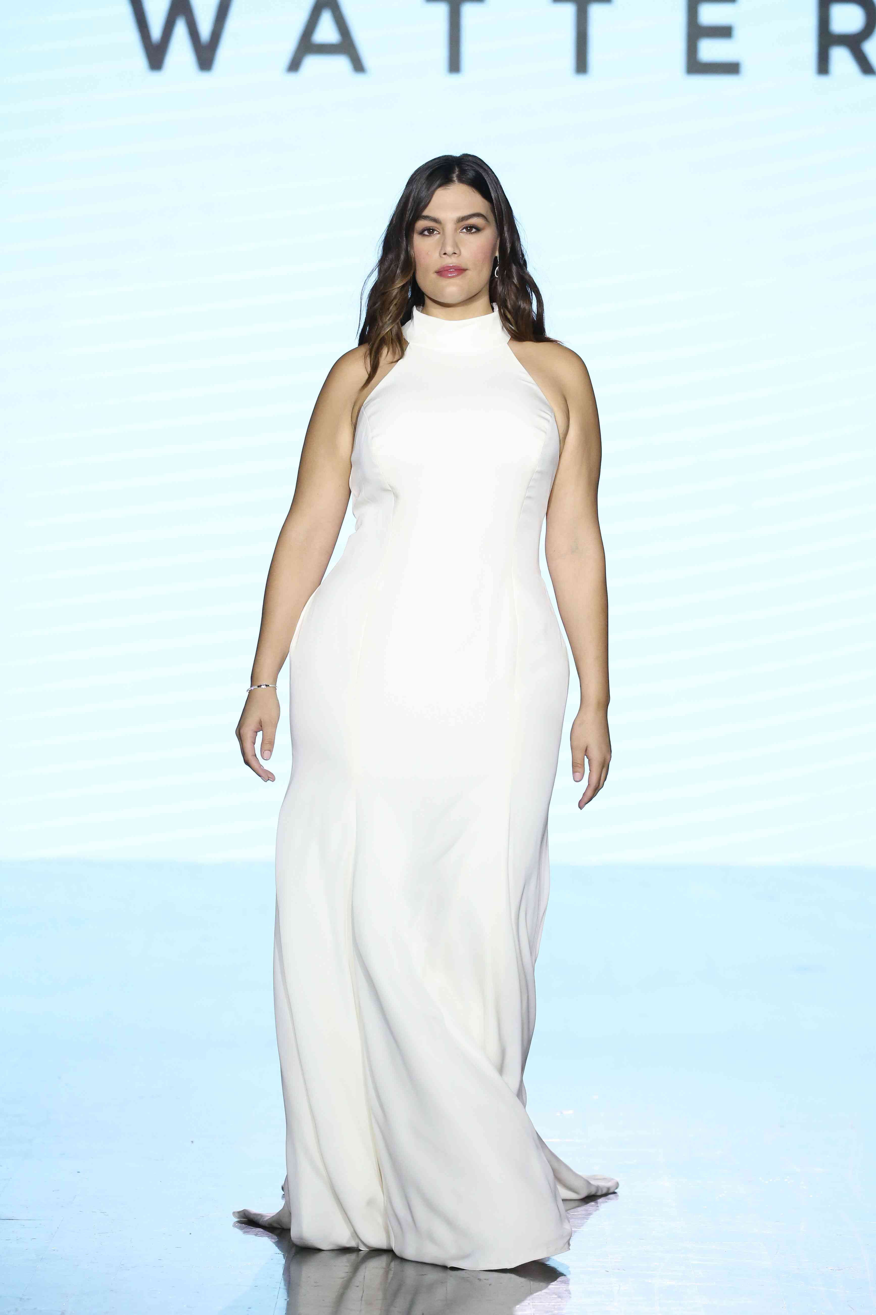 Model on runway in fitted high-neck satin sheath gown