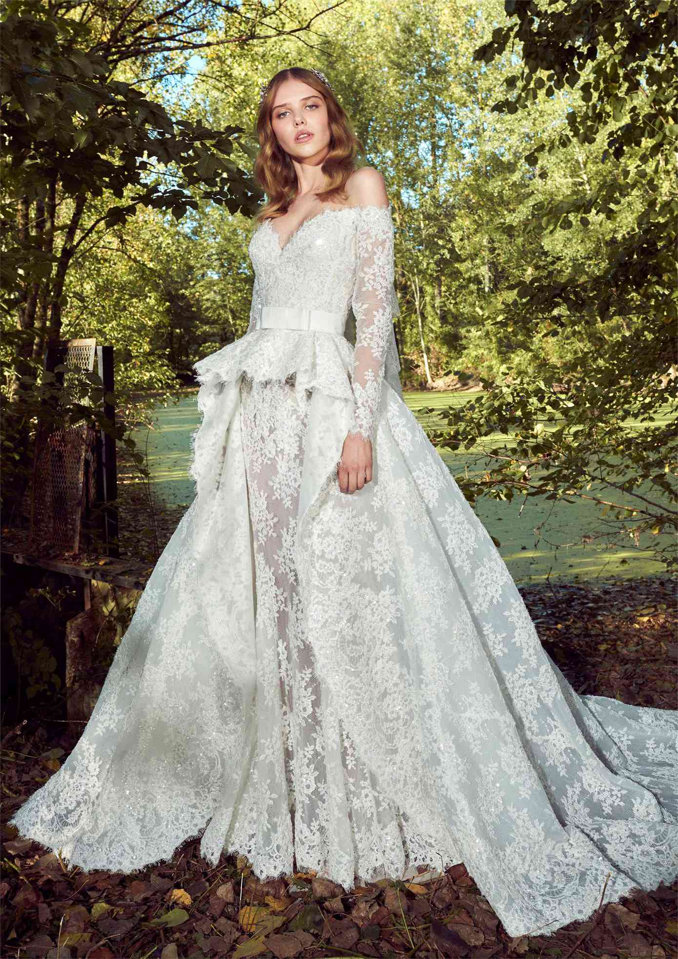 Model in allover lace gown with long off-the-shoulder sleeves and a voluminous overskirt with an eyelash lace trim