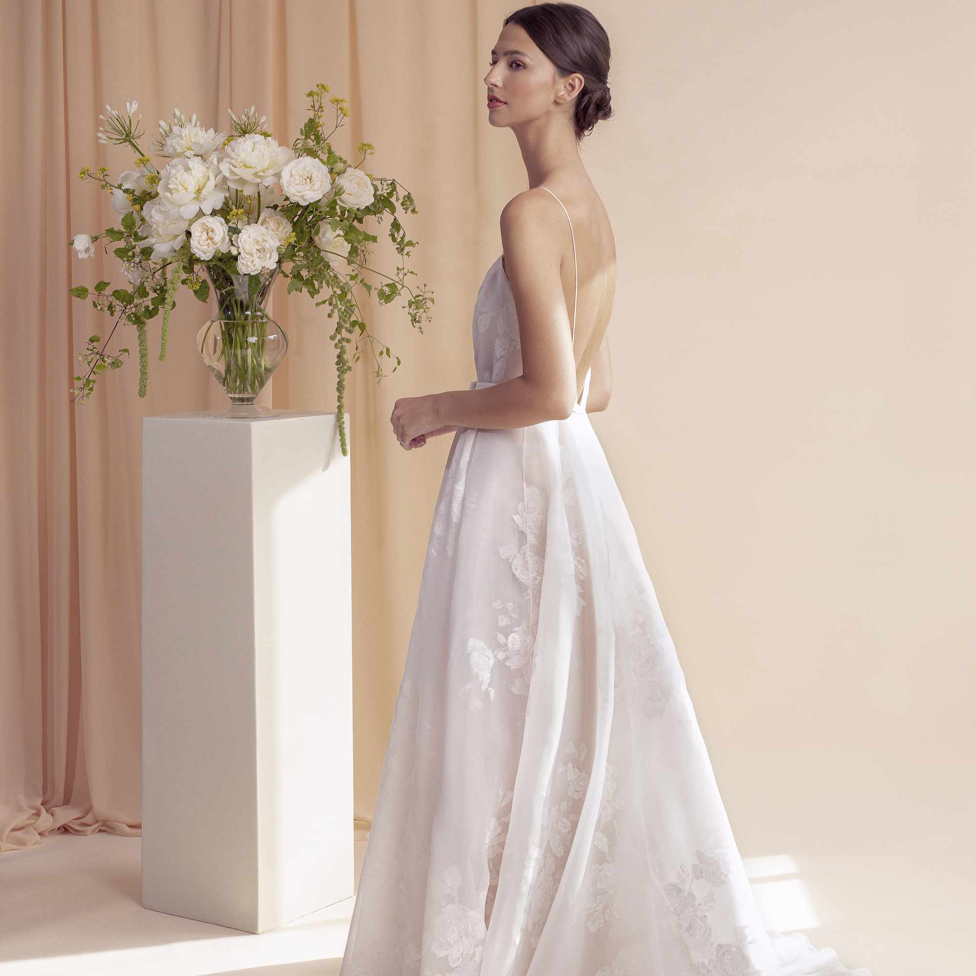 Woma wearing white sleeveless bridal gown next to a pillar with a white floral arrangement on top.