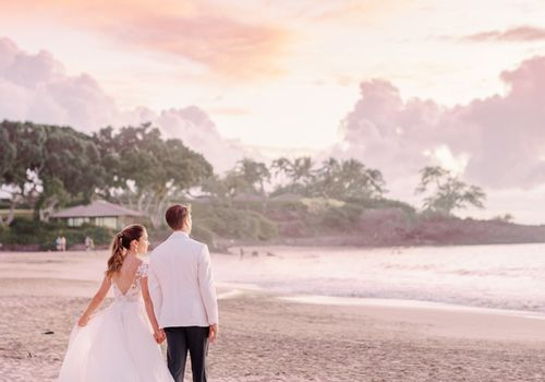 Bride and groom looking over sunset beach