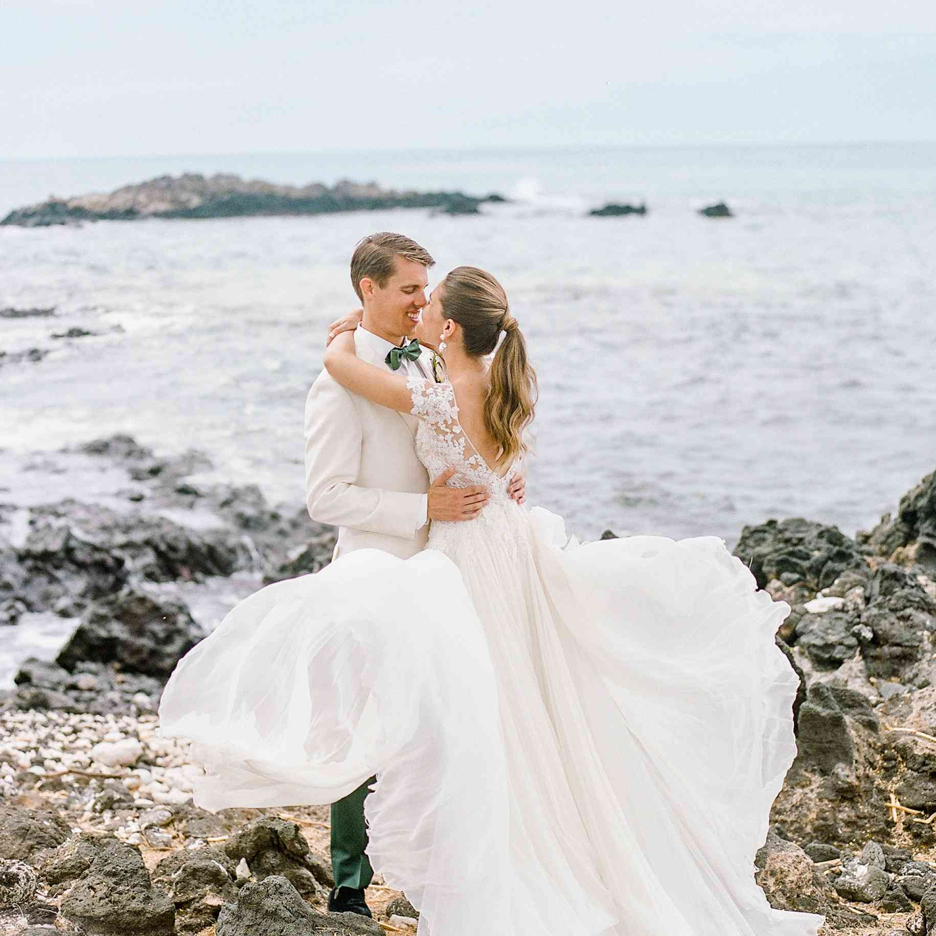 bride and groom standing on rocky beach
