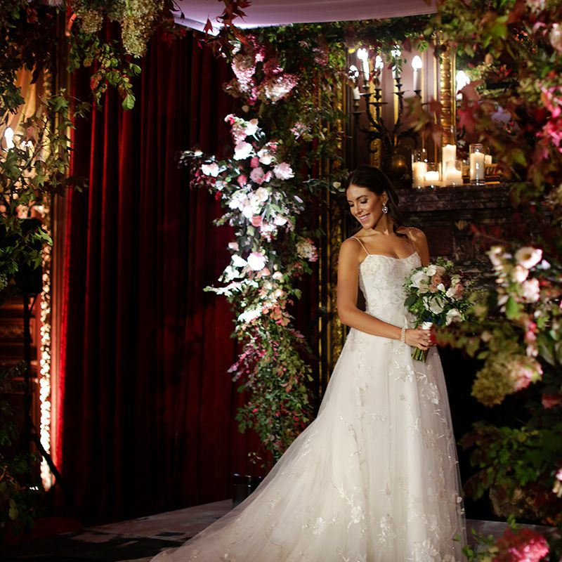 Portrait of a bride looking over her shoulder under a floral arch