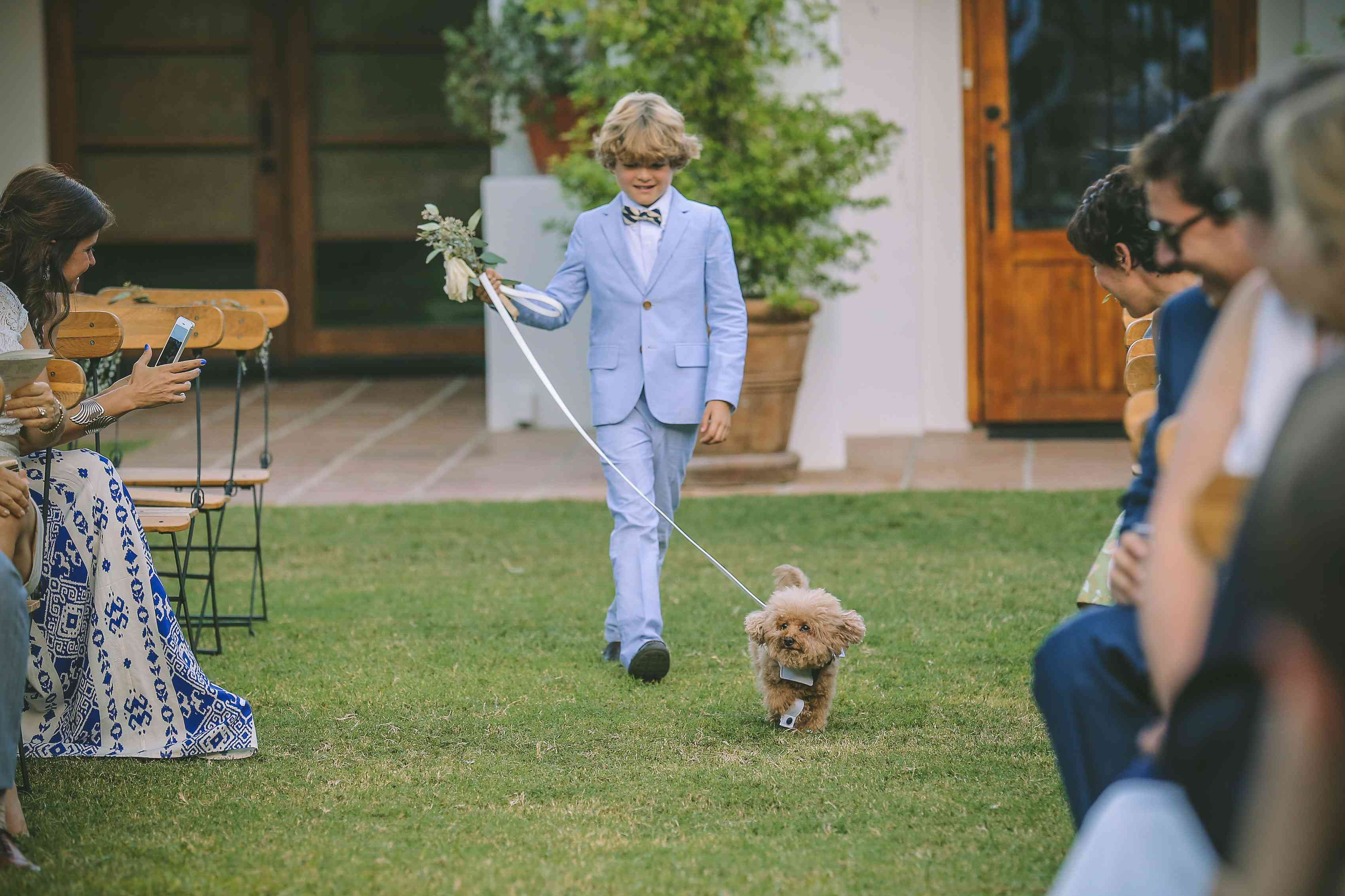 Puppy being walked down aisle by page boy