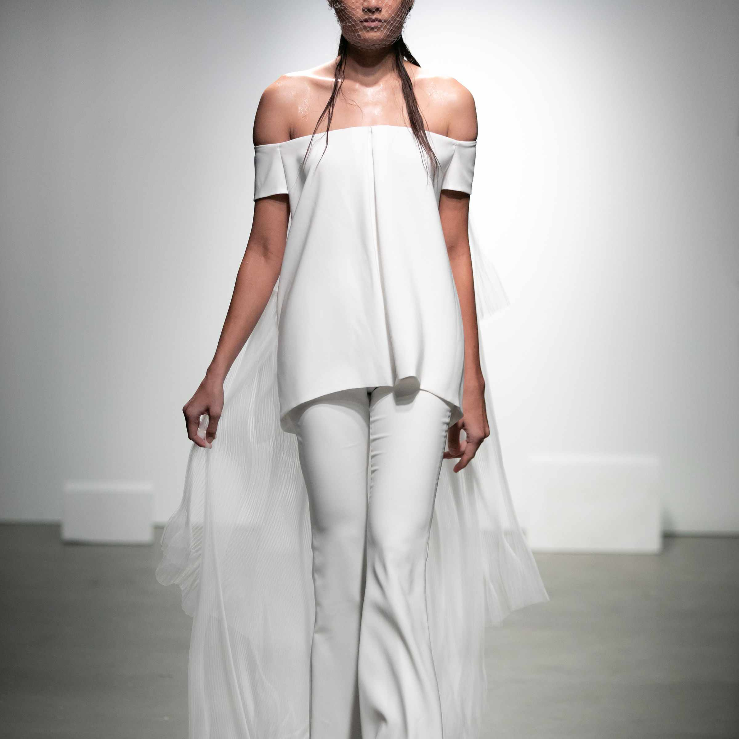 Model in crepe off-the-shoulder top and pants with a pleated tulle train