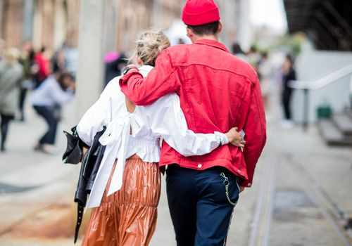 two people walking together with arms around each other