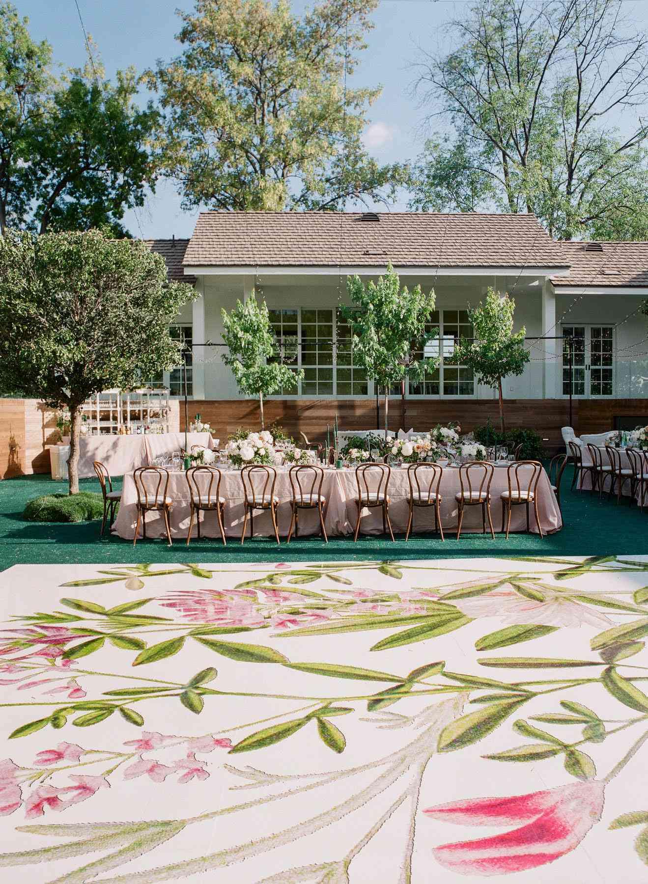 A dancefloor at an outdoor wedding with floral design