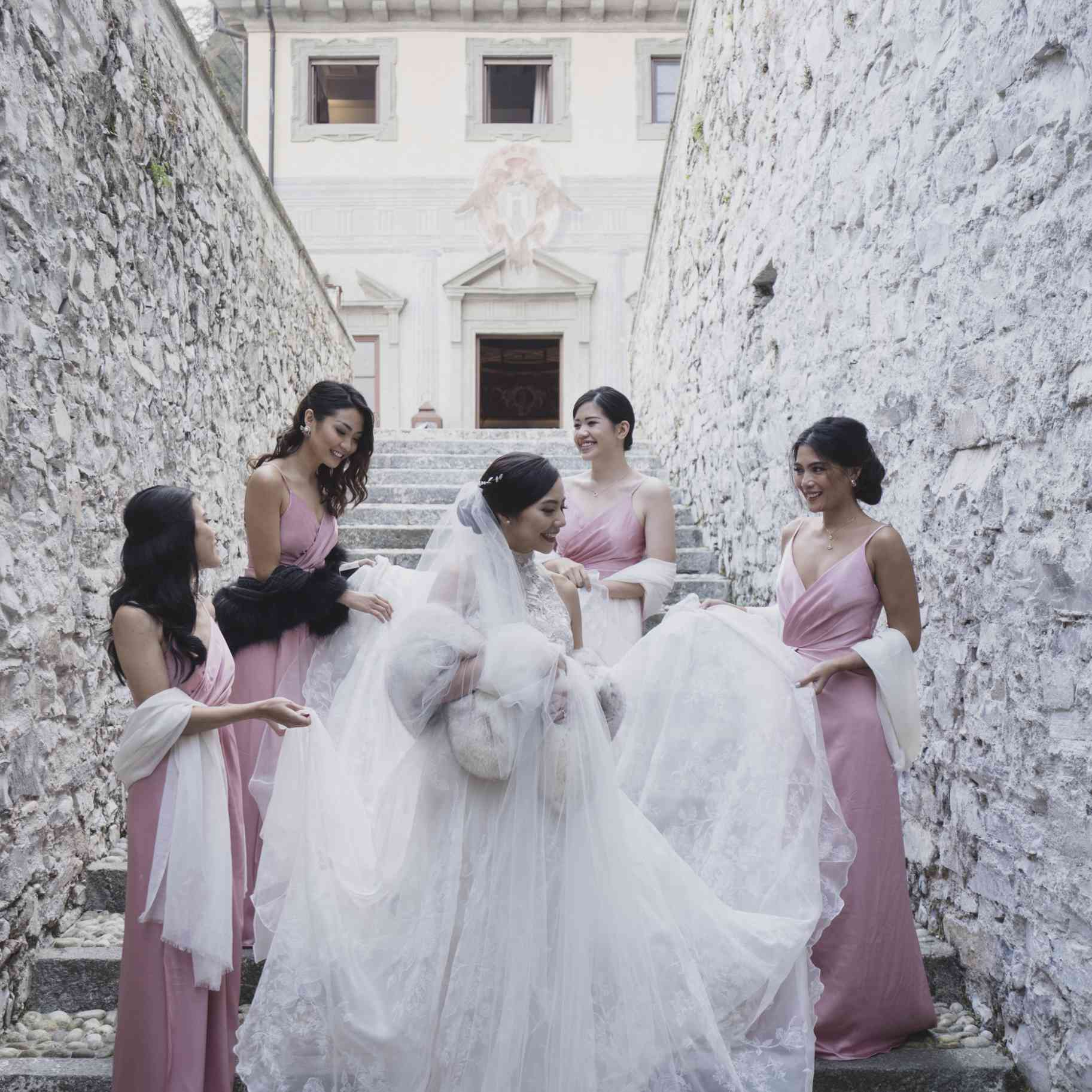 Bride with bridesmaids on stone steps