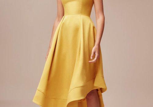 Model in midi yellow strapless dress