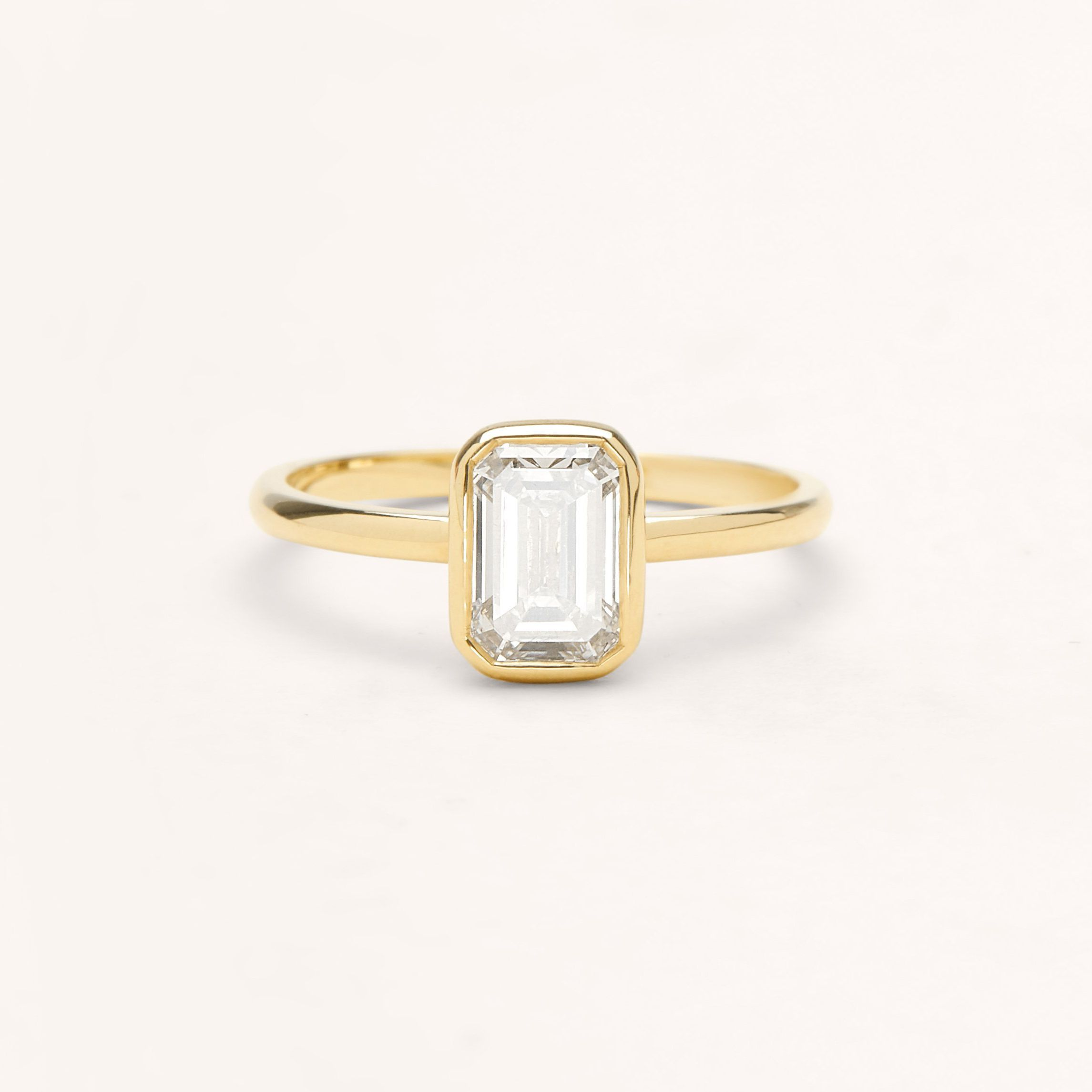 Bezel emerald cut diamond engagement ring with yellow gold band on a white background.