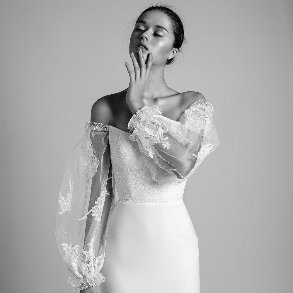 Model in fitted corset wedding dress with oversized sheer lace and tulle sleeves
