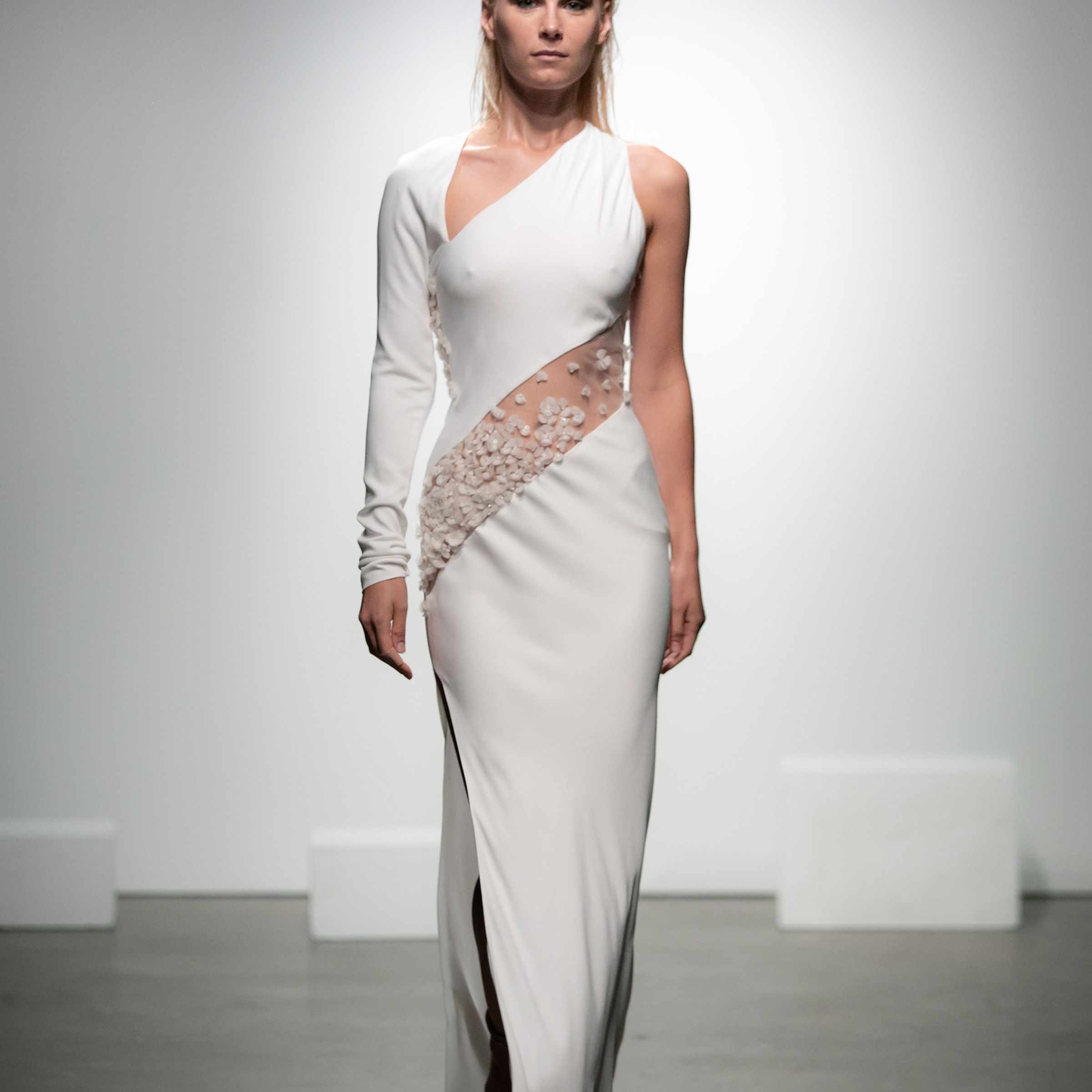 Model in one-sleeved asymmetrical crepe dress with embroidered tulle ribbon on torso