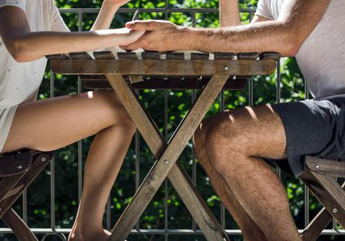 A couple holding hands while sitting at a table outside.