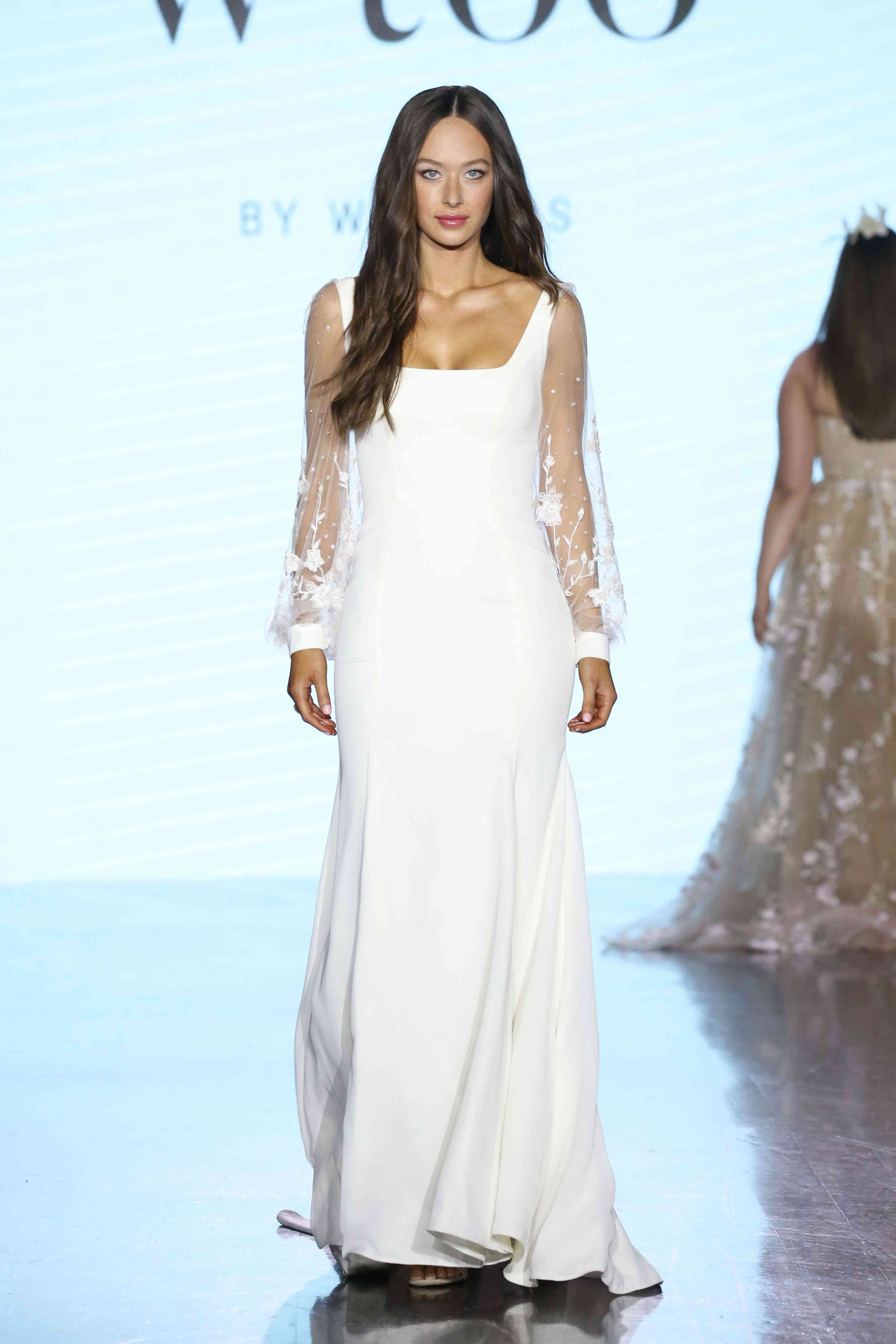 Model in a crepe wedding gown with a square neckline and floral embroidered illusion long sleeves