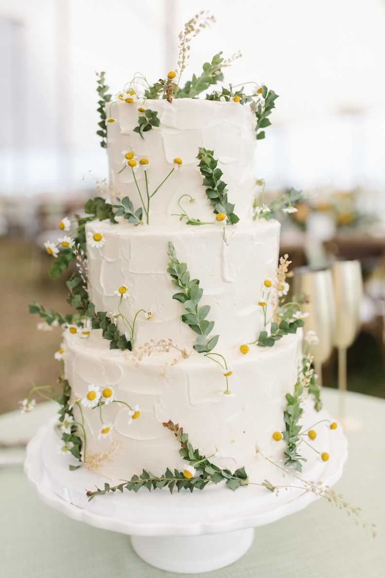 Three-tiered white cake decorated with chamomile leaves and flowers