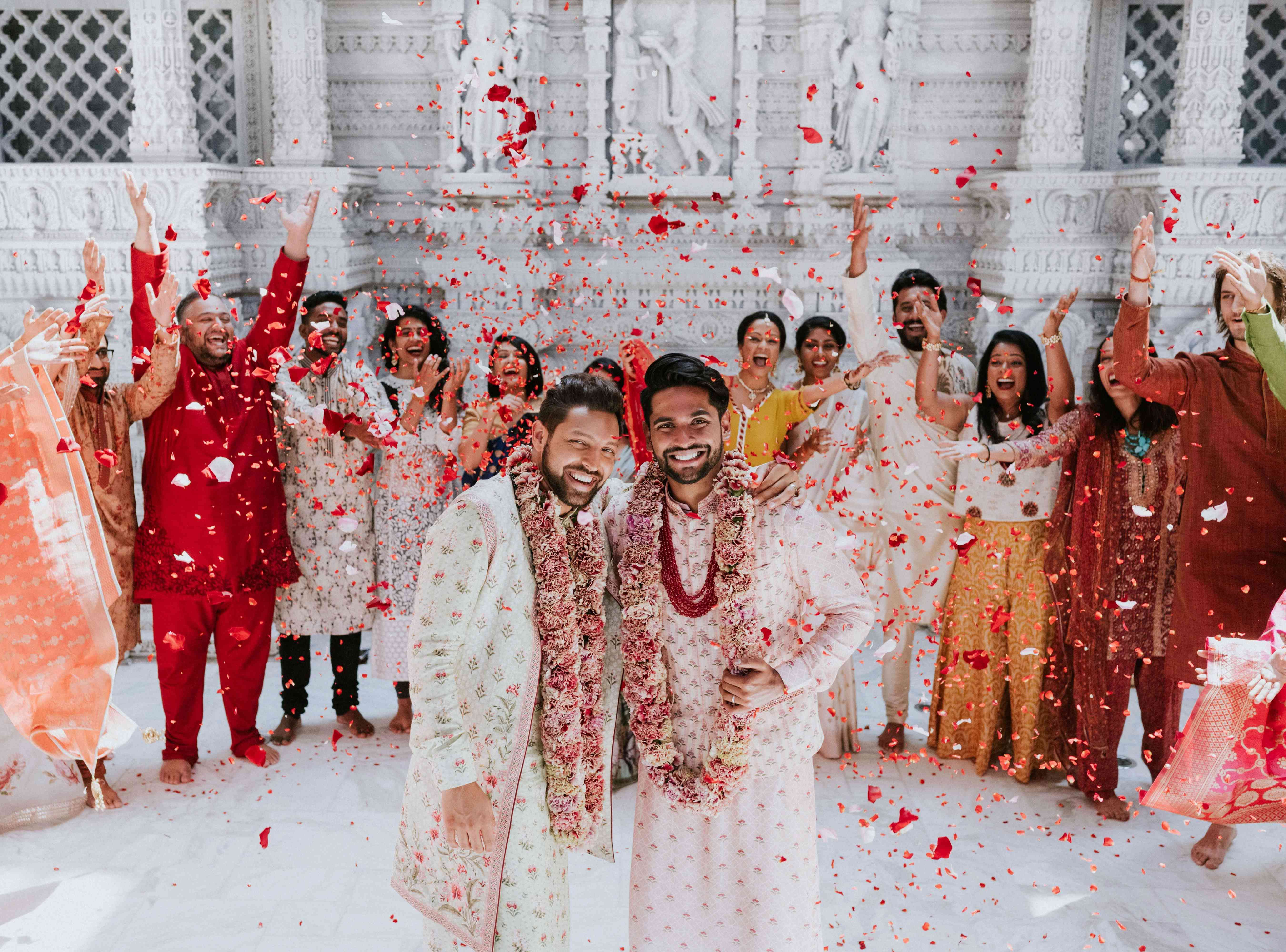 A gay Hindu couple at their wedding inside a temple while guests throw red petals in the air
