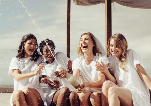 Bride popping a bottle of champagne with three women at a bachelorette party