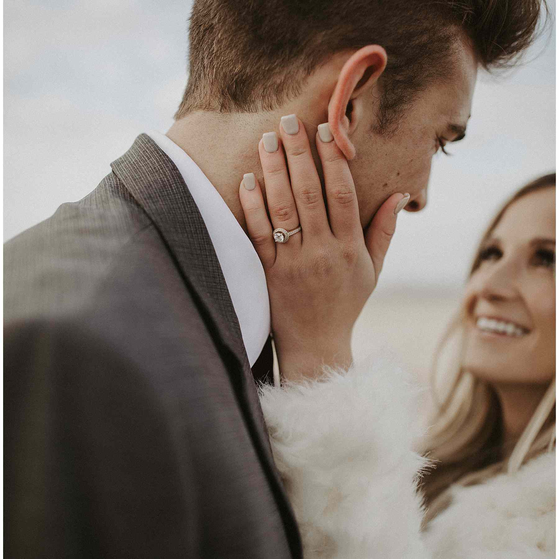 Bride with soft gray manicure holding her hand to her groom's cheek