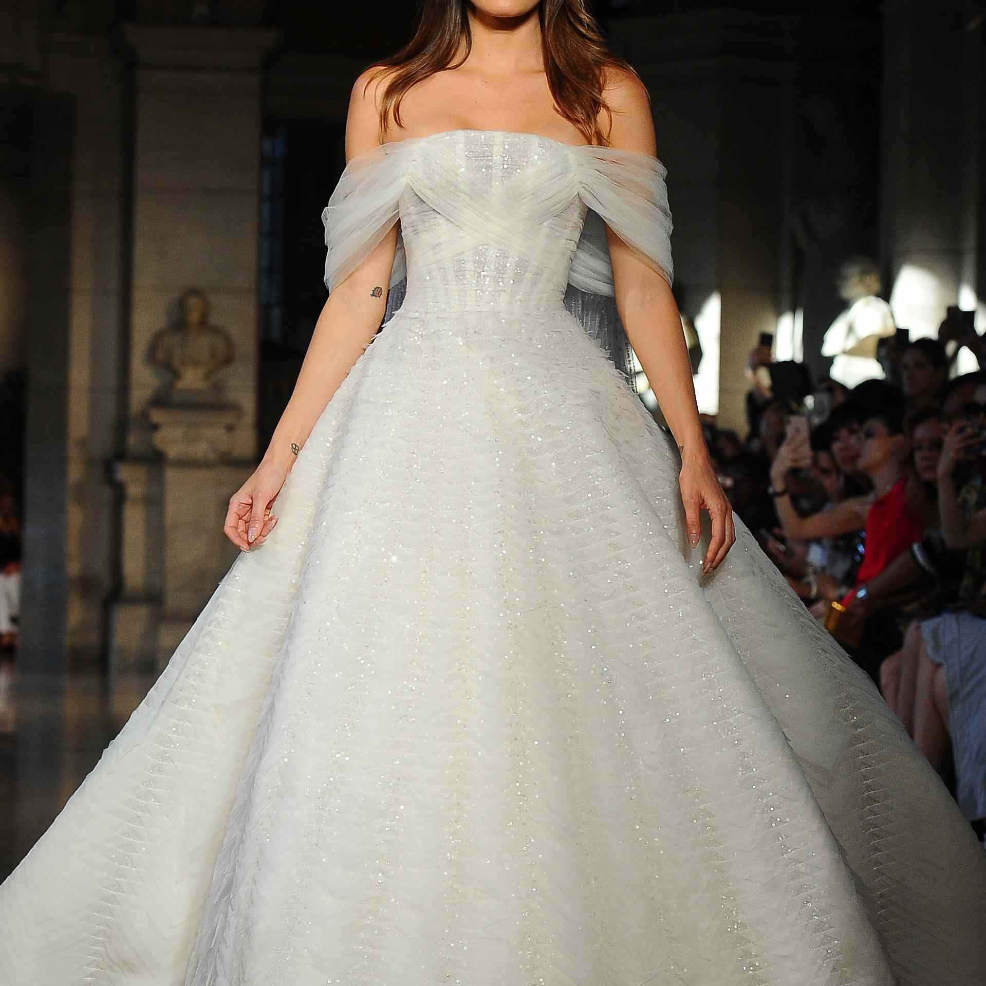 A model walks the runway in off-the-shoulder princess wedding gown