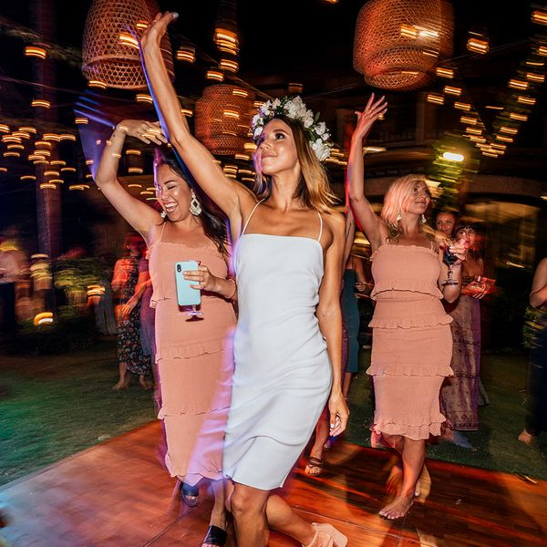 Bride and bridesmaids dancing at outdoor nighttime reception