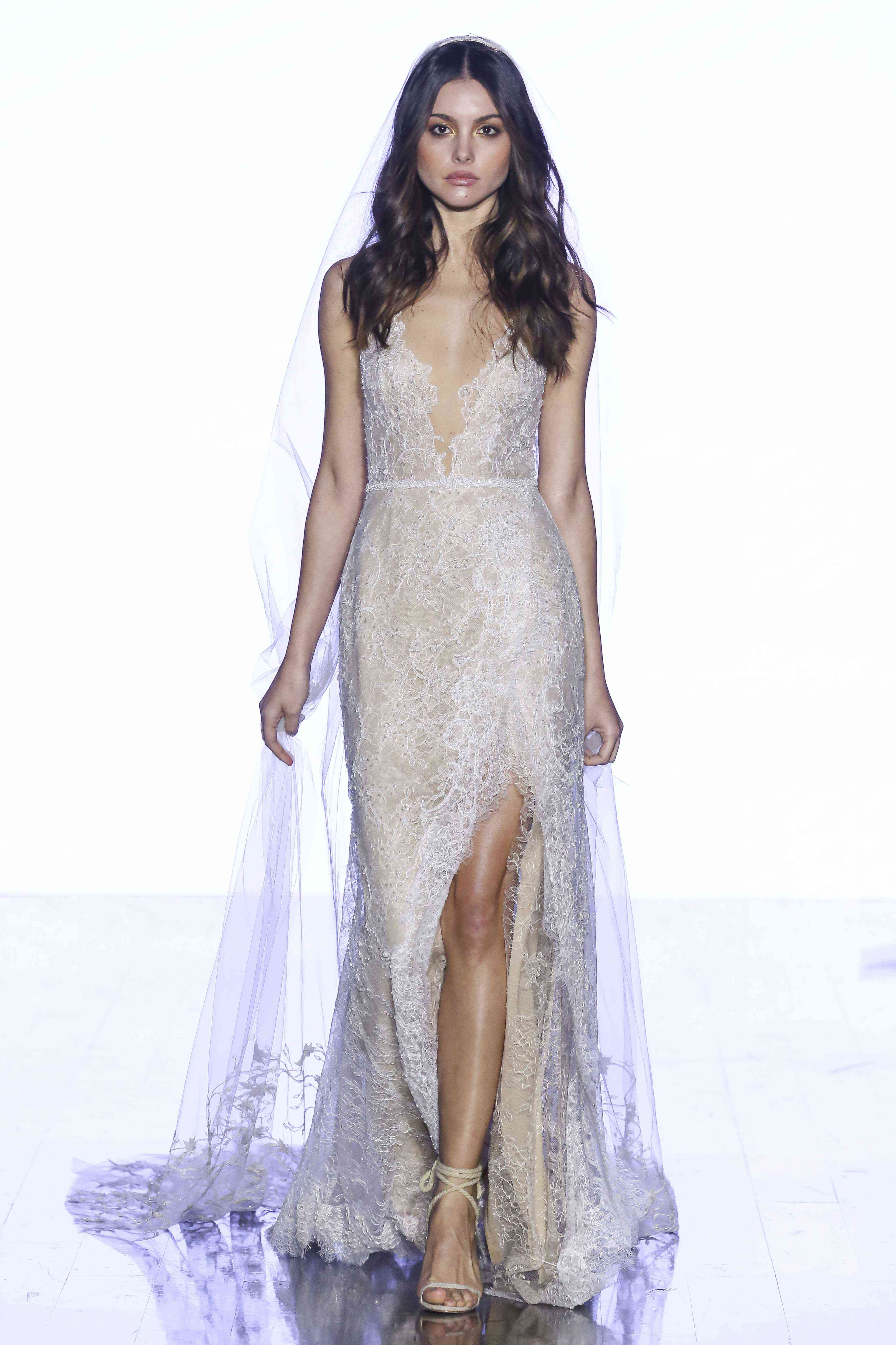 Model in V-neck beaded lace sheath gown with front skirt slit