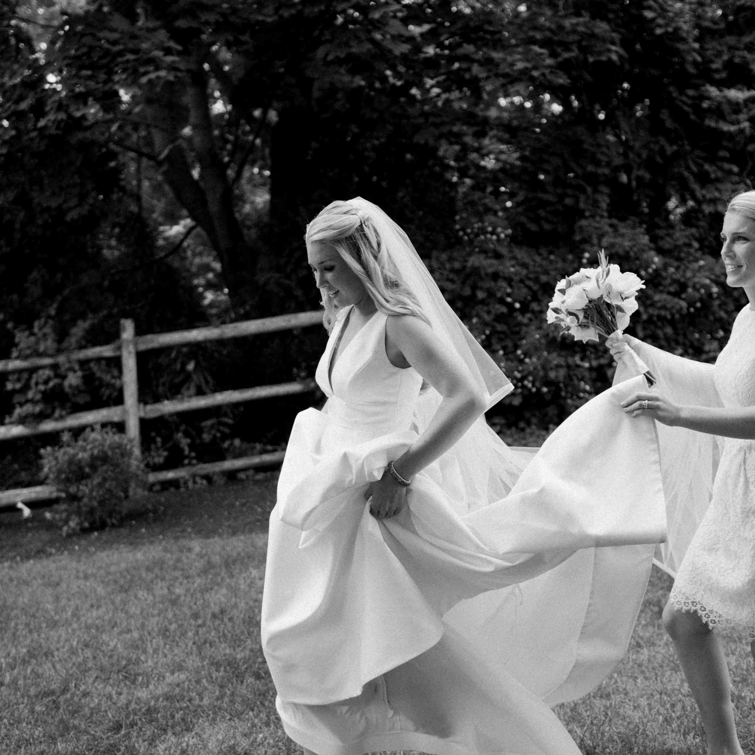Bridesmaid holding bride's train