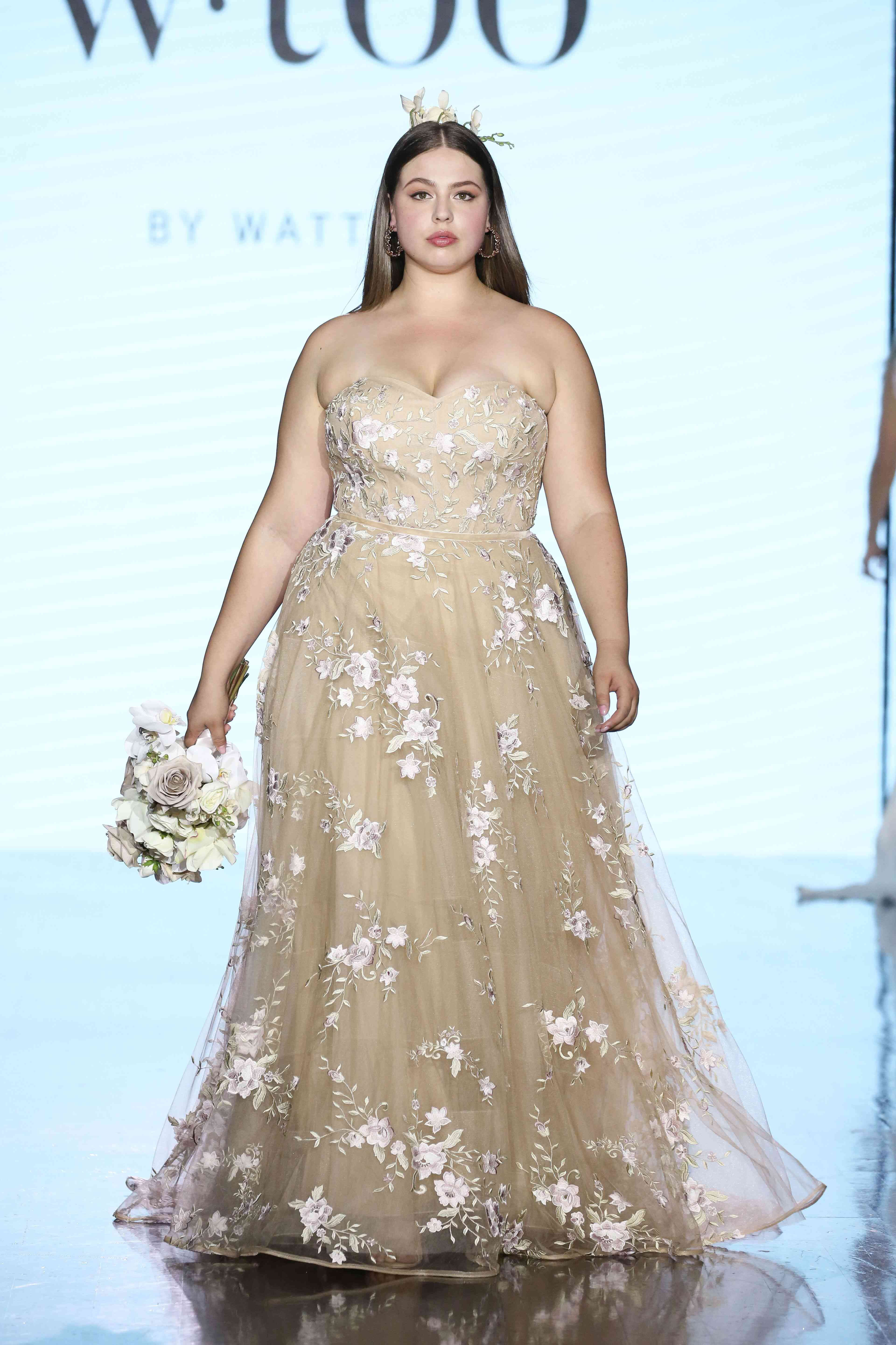 Model in strapless gold tulle ballgown with floral appliques