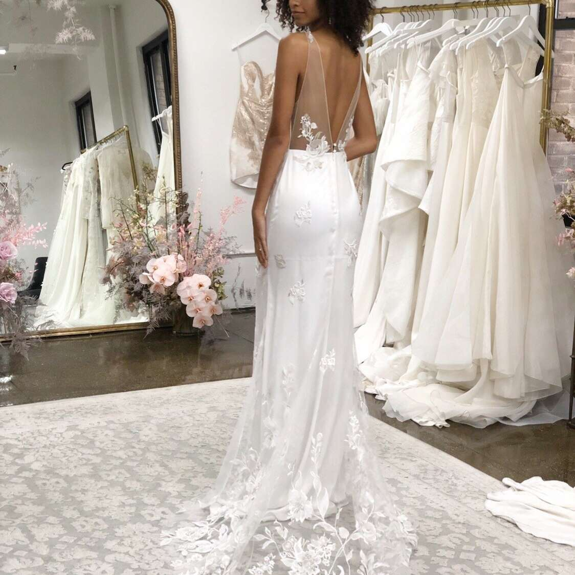 Model in bridal gown with sheer train with floral embroidery