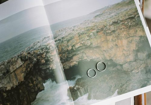Two wedding rings on a photo of rocks by the ocean