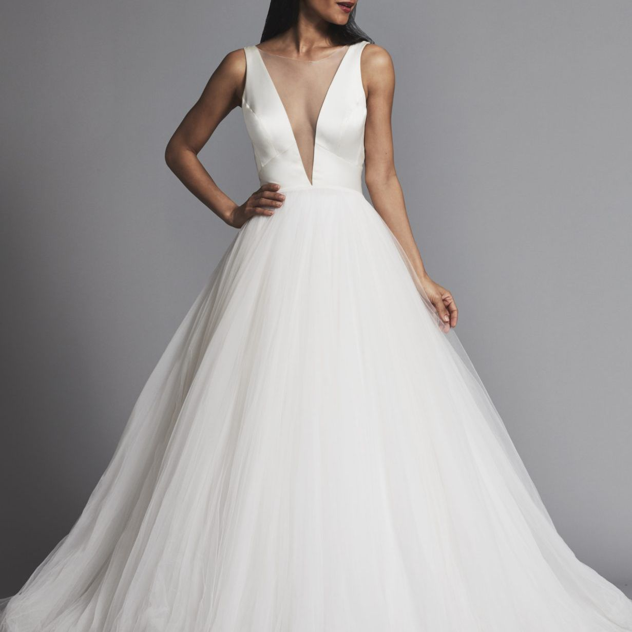 Model in satin and tulle ballgown wedding dress with sheer illusion neckline