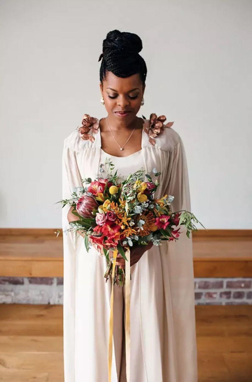 Bride in nude ensemble holding vibrant bouquet