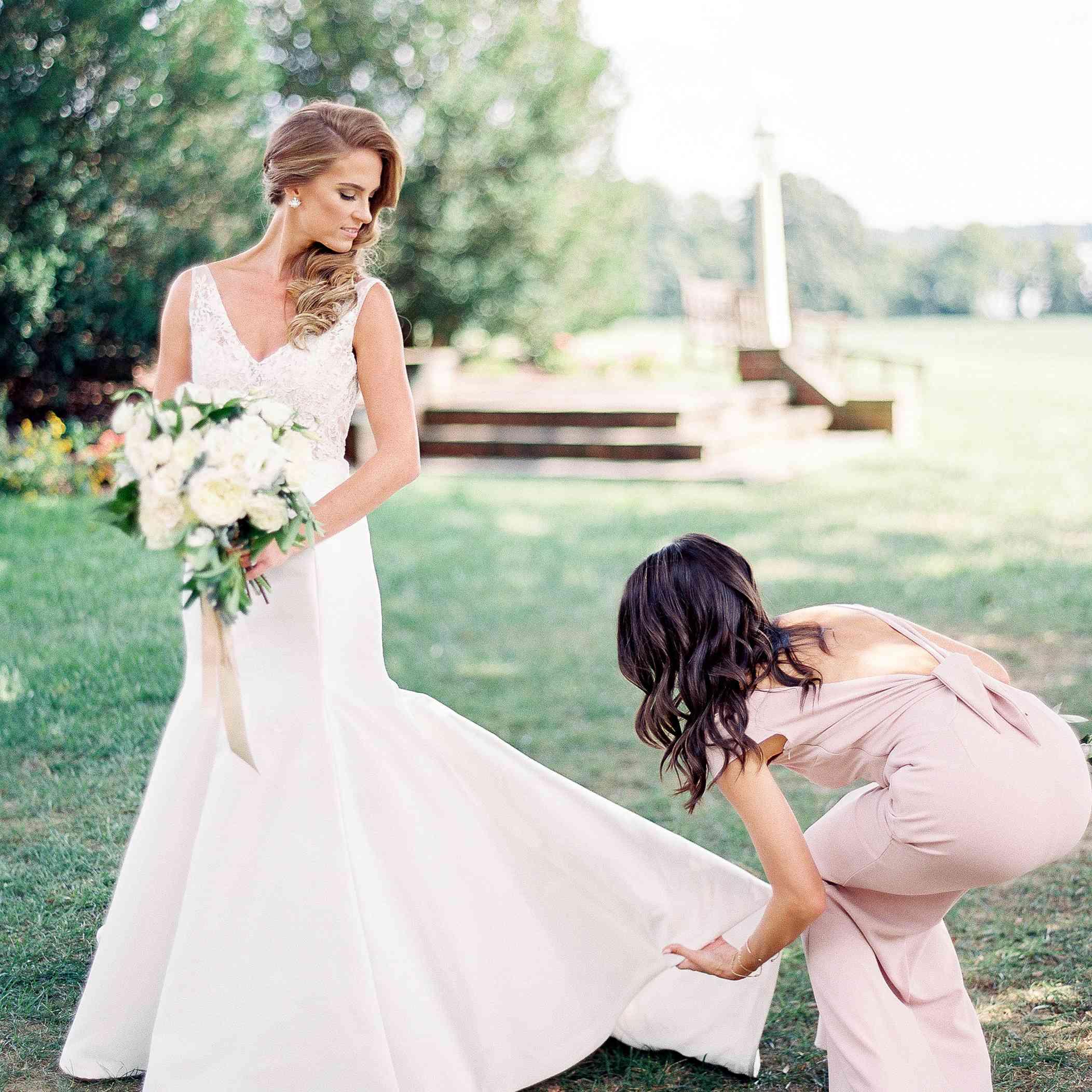 <p>bridesmaid helping bride get dressed</p>