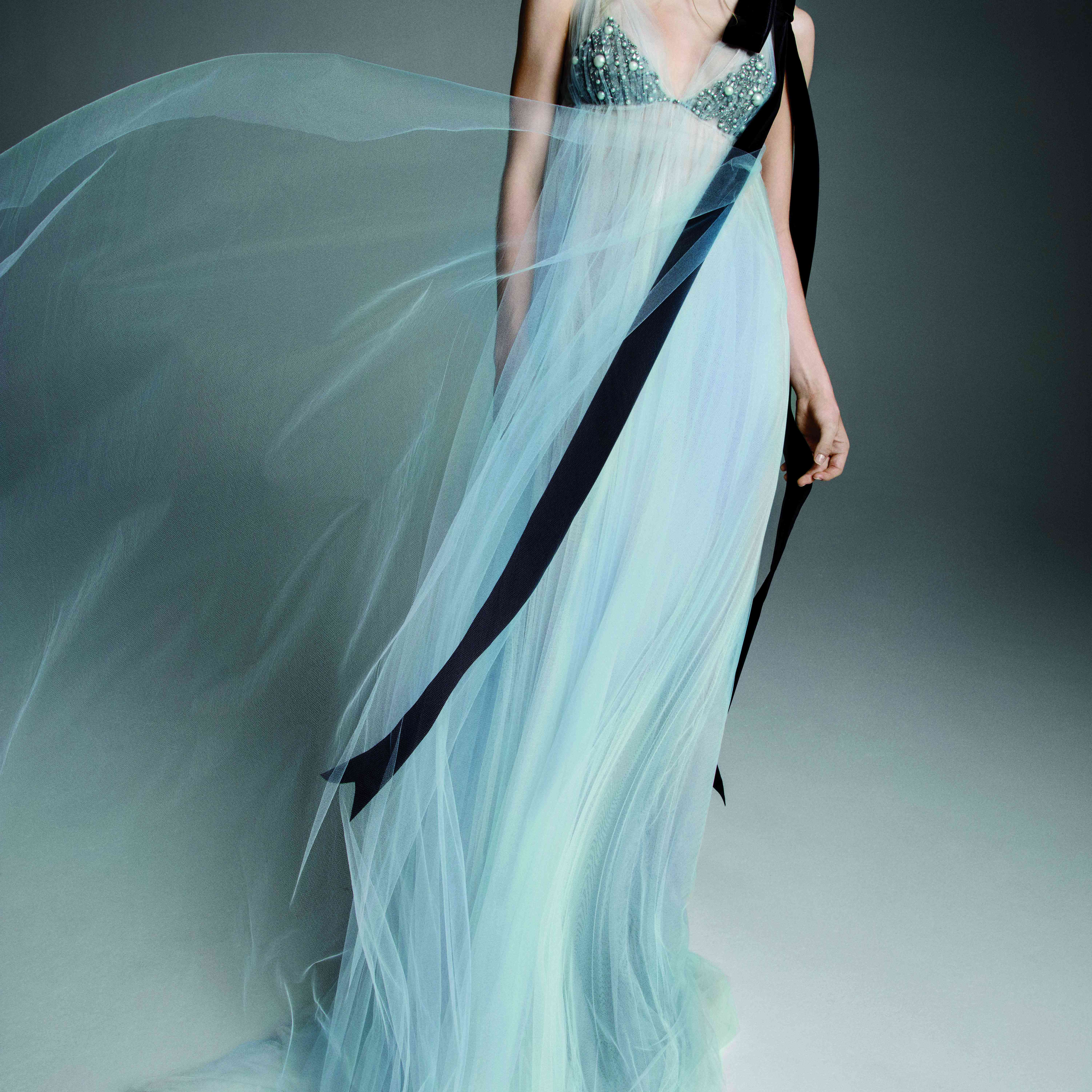 Model in light blue tulle empire-waist gown with a jeweled bust and black velvet ribbon accent at the shoulder
