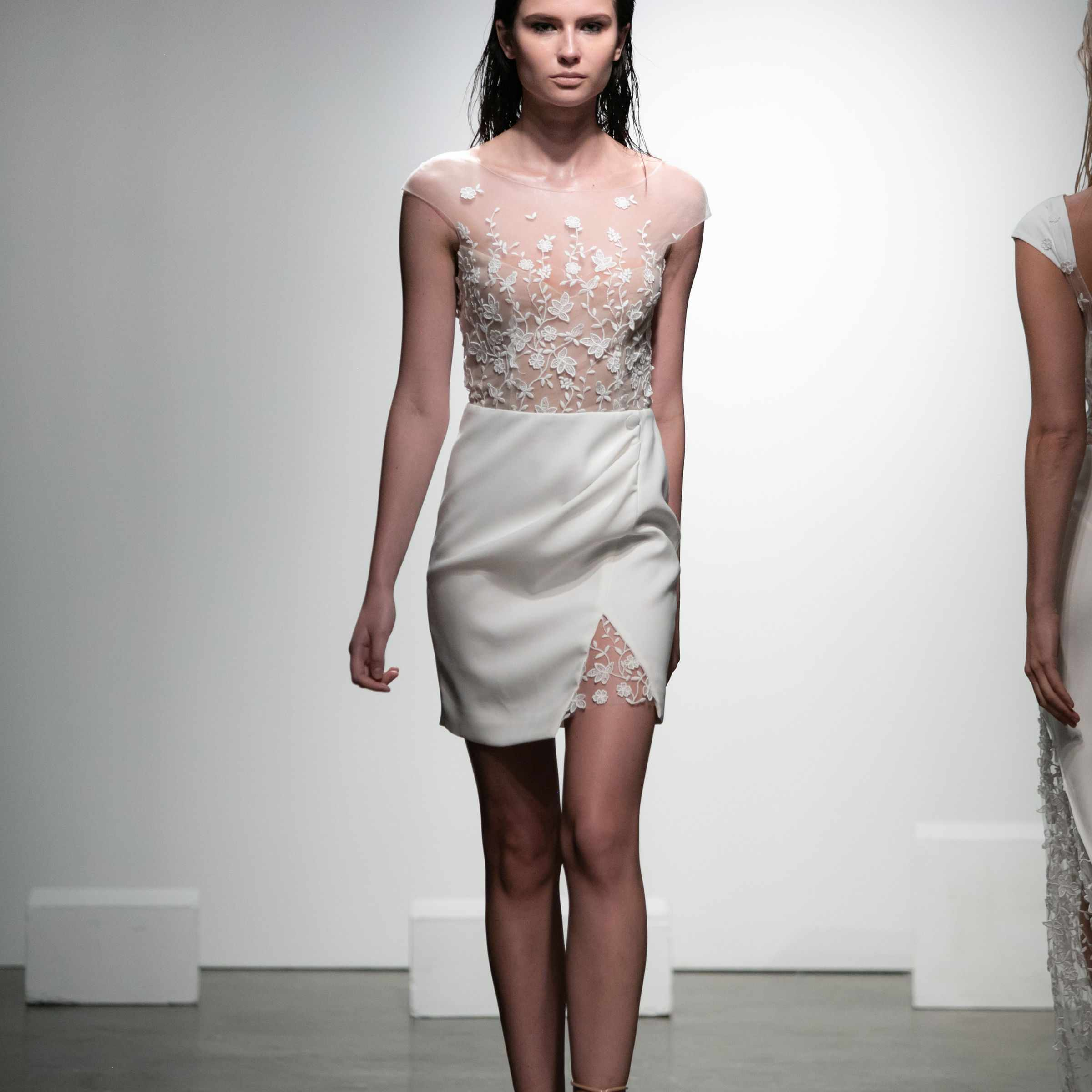 Model in mini crepe dress with wrap effect see-though top in 3D embroidered tulle