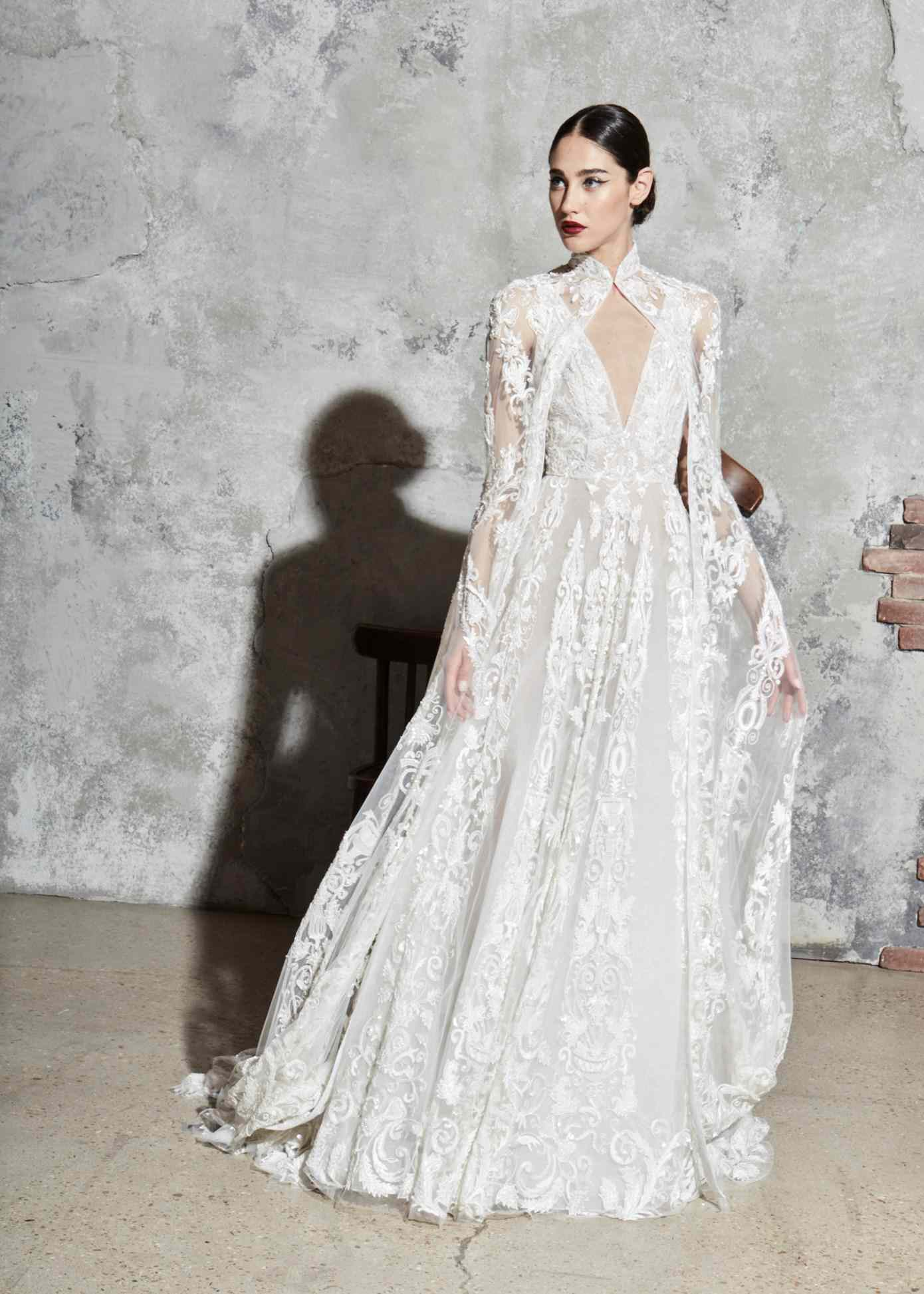Model in a sleeveless V-neck embroidered tulle gown with a matching cape