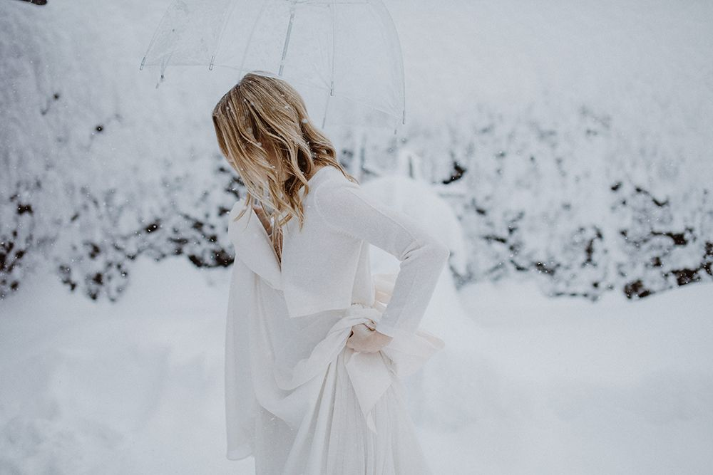 Profile of bride outside while snowing holding a clear umbrella